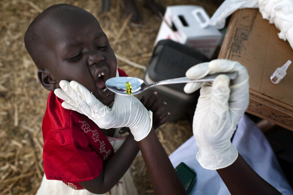 A South Sudanese child receives a dose of vitamin A given by Medecins Sans Frontieres (MSF, doctors without borders) in an isolated makeshift IDP camp for Dinka ethnic group placed in an island between Bor and Minkamman, South Sudan, on March 5, 2014. Heavy fighting broke out in the main military barracks in war-torn South Sudan's capital Juba on Wednesday, underscoring serious tensions within the national army as it battles a rebel uprising. Fierce gunfire was heard coming from the main barracks near Juba University, home to the presidential guards and other elite troops, from 9:30 am (0630 GMT), with the shooting ending two hours later. The government played down the violence. AFP PHOTO / JM LOPEZ        (Photo credit should read JM LOPEZ/AFP/Getty Images)