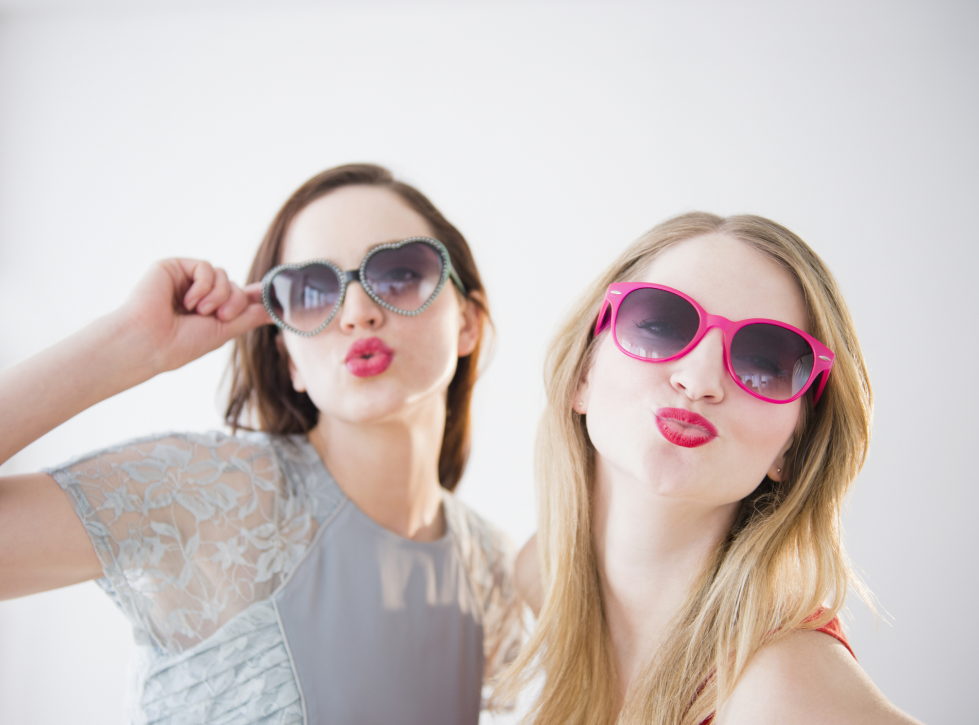 The expression displayed by the women in this stock photo is sometimes described as a duck face.