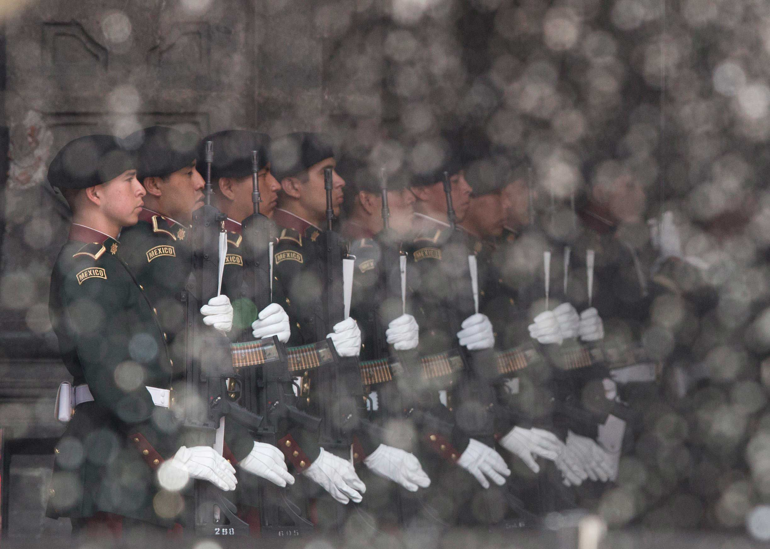 Oct. 31, 2014. Members of a Mexican honor guard stand behind the spray from a water fountain during a welcoming ceremony for El Salvador's President Salvador Sánchez Cerén at the National Palace in Mexico City.