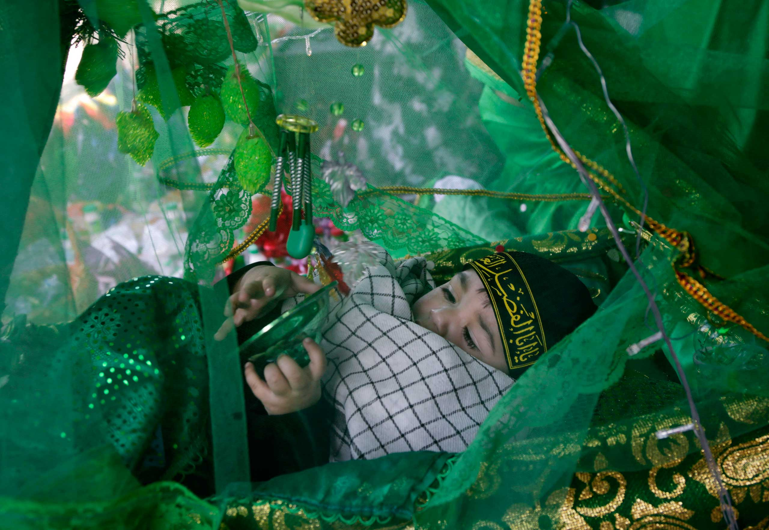Nov. 3, 2014. A Bahraini baby, laid for a blessing in a bassinet that is part of a living diorama, plays with ornaments, ahead of the Ashoura holiday during the month of Muharram, in Malkiya, Bahrain.