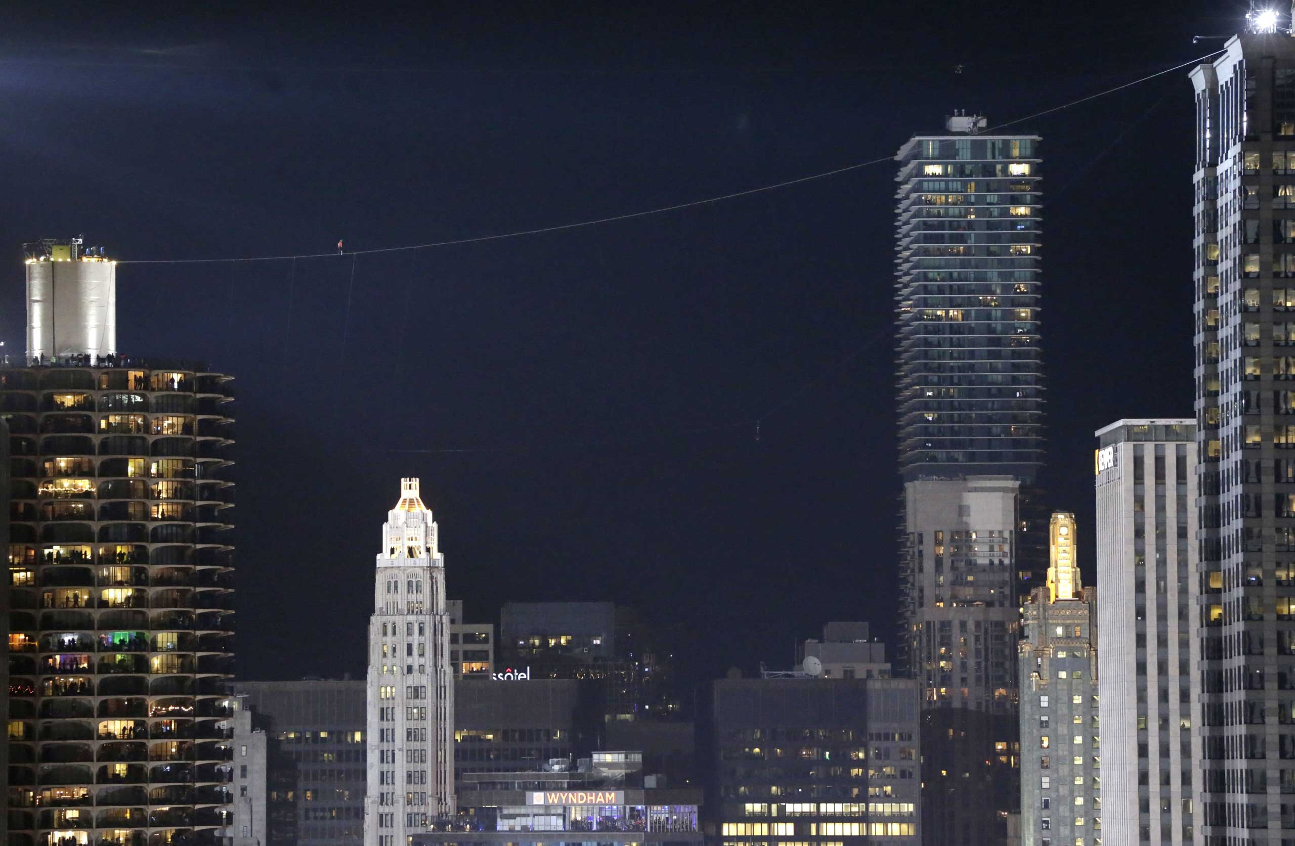 Nov. 2, 2014. Daredevil Nik Wallenda, left center in red, makes his tightrope walk uphill at a 19-degree angle, from the west tower at Marina City across the Chicago River to the top of the Leo Burnett Building in Chicago.