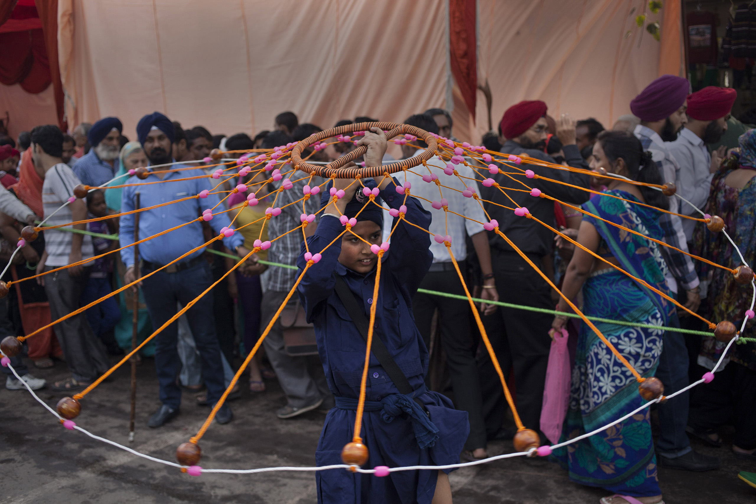 An Indian Sikh boy displays his martial art skills during a religious procession on the eve of the birth anniversary of Guru Nanak, the first Sikh Guru, in New Delhi, India on Nov. 5, 2014.