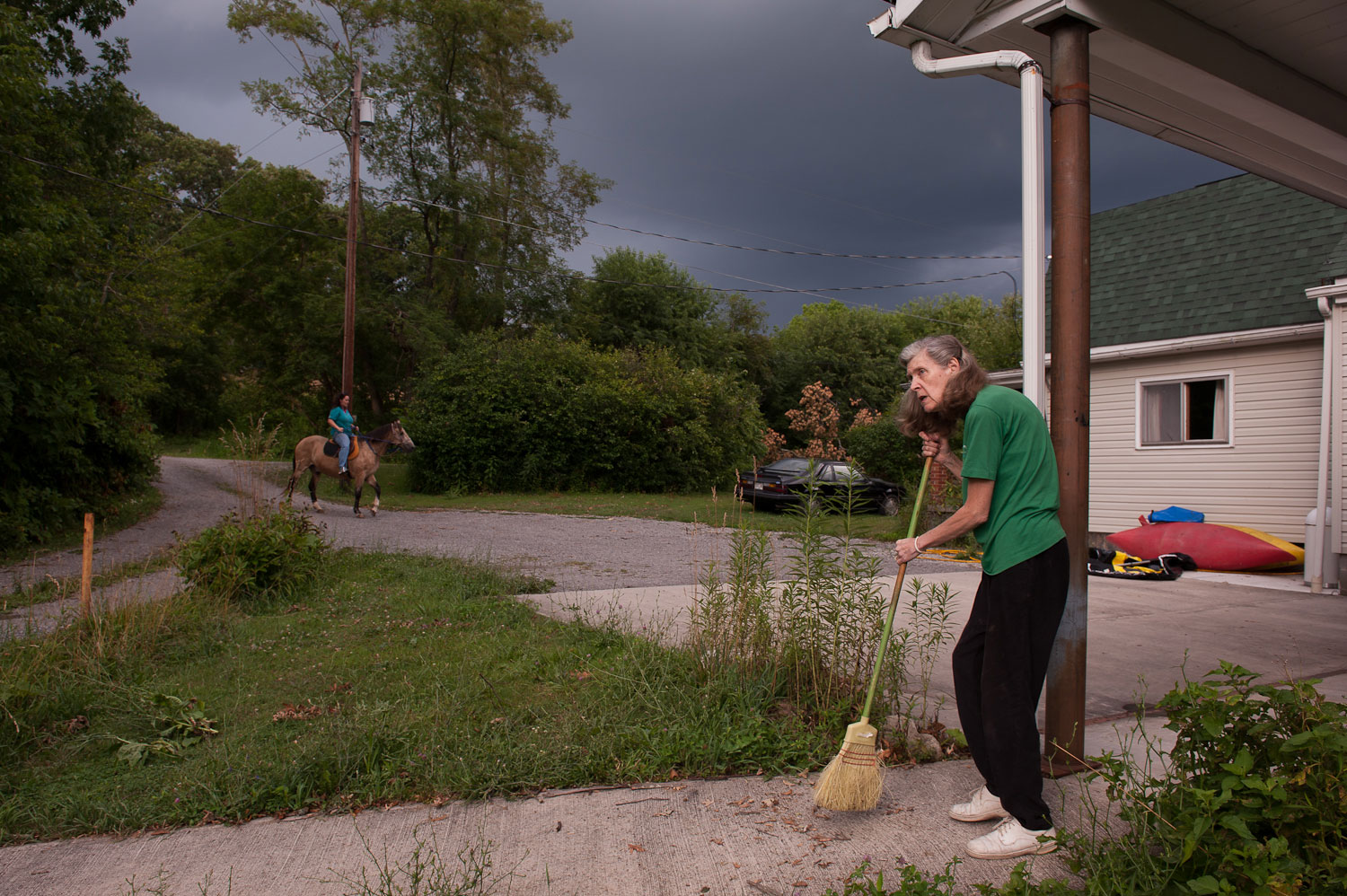 Eleanor Copeman sweeps the porch outside the family home as her daughter rides her horse toward the house in Elkins, West Virginia, on July 14, 2012.