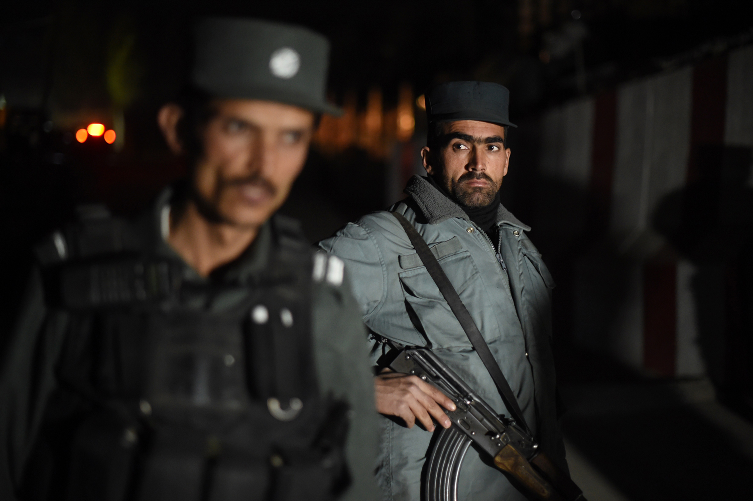 Afghan policemen stand guard at the site of a suicide attack at a foreign guesthouse in Kabul on November 27, 2014.