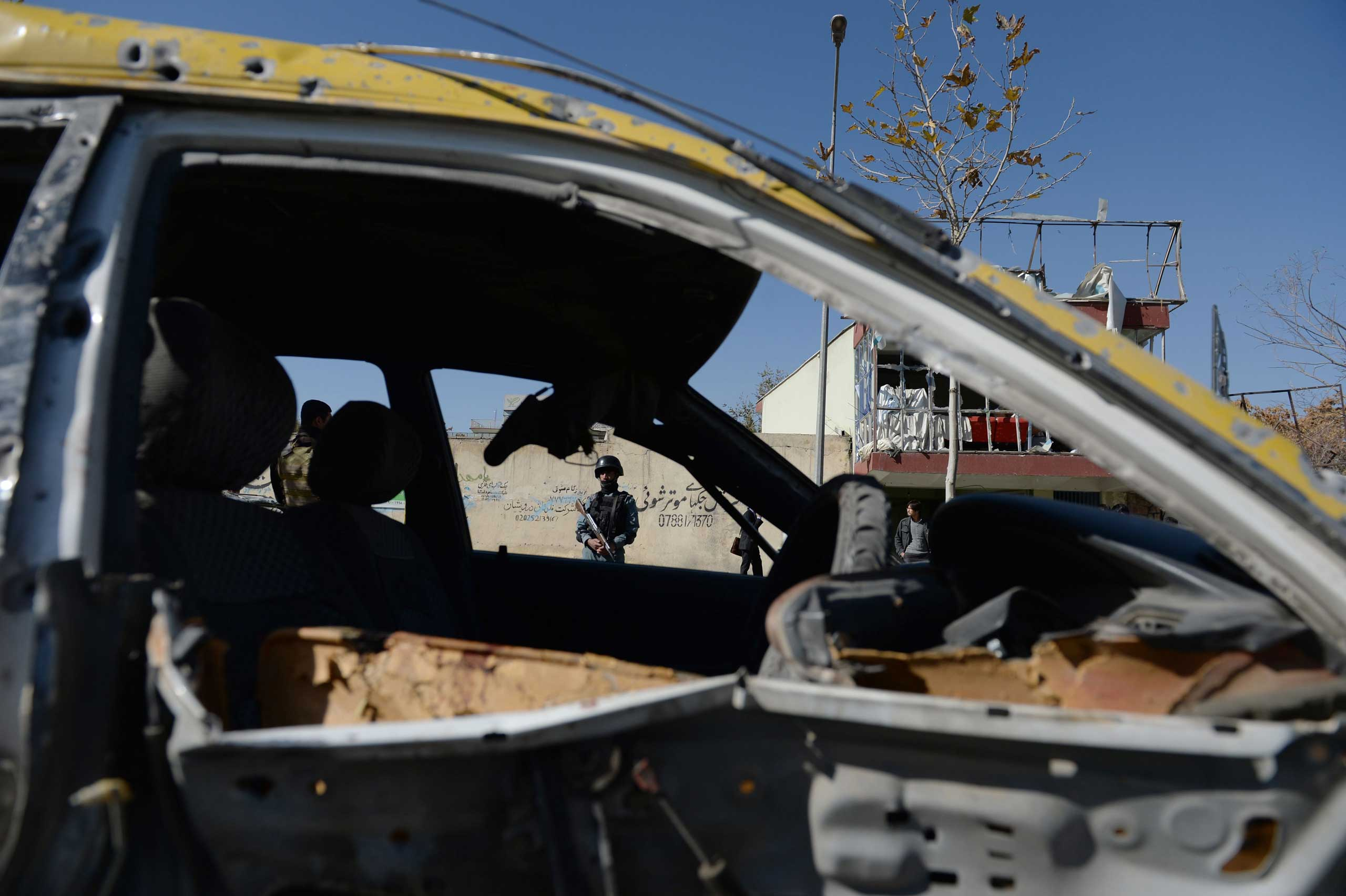 An Afghan policeman is seen through the wreckage of a taxi which was destroyed by a suicide attack targeting a vehicle convoy of Afghan lawmakers in Kabul, Afghanistan on Nov. 16, 2014.