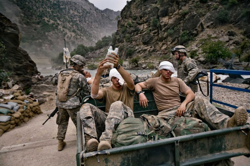 AUGUST 2006: Three wounded U.S. Army soldiers from the 10th Mountain Division await evacuation by helicopter from Kamdesh, Nuristan province. They were ambushed and suffered wounds to their eyes and foreheads.  (Photo by Robert Nickelsberg)