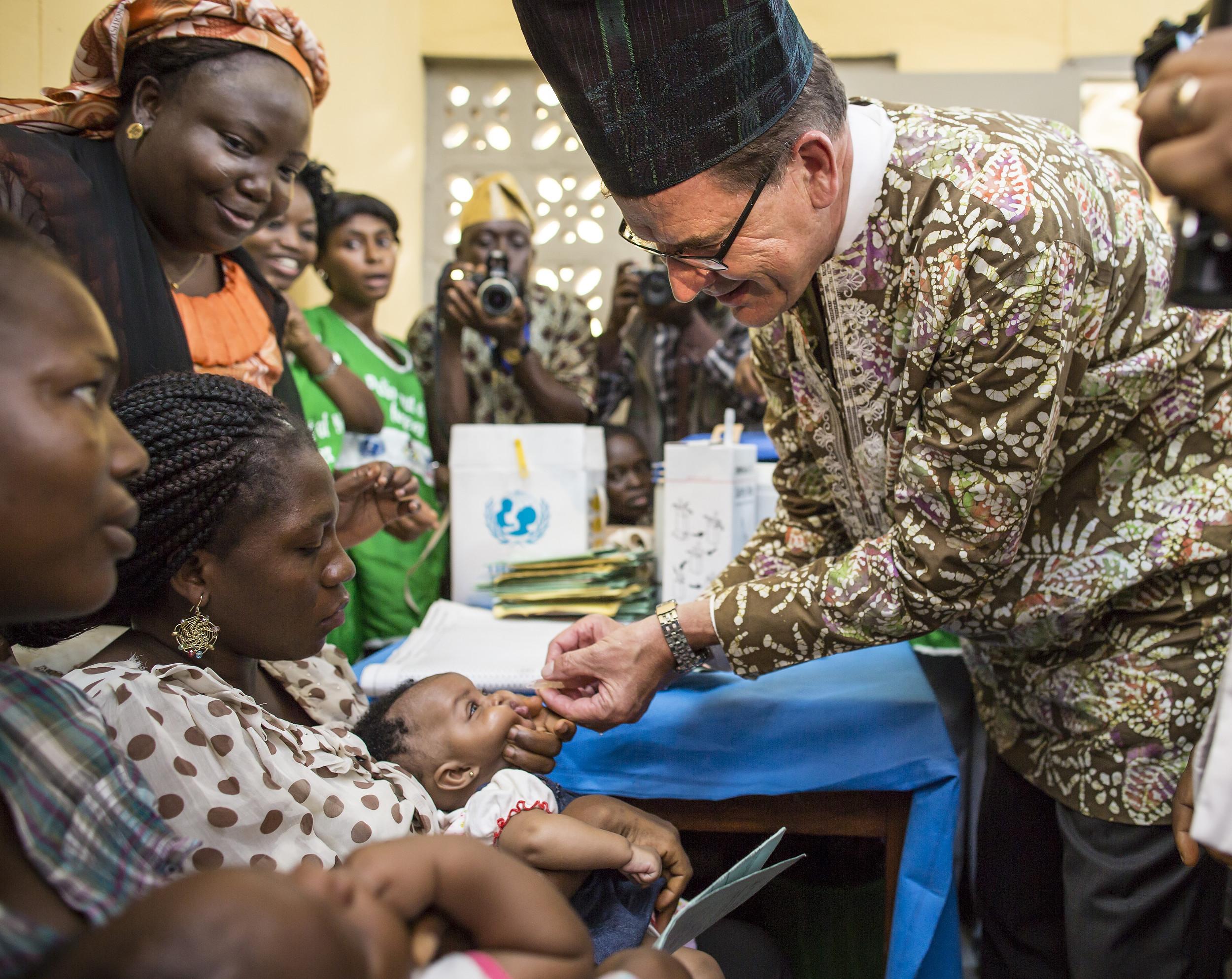 German Development Minister Gerd Mueller vaccinates a child against polio in a hospital on June 11, 2014 in Abeokuta, Nigeria.