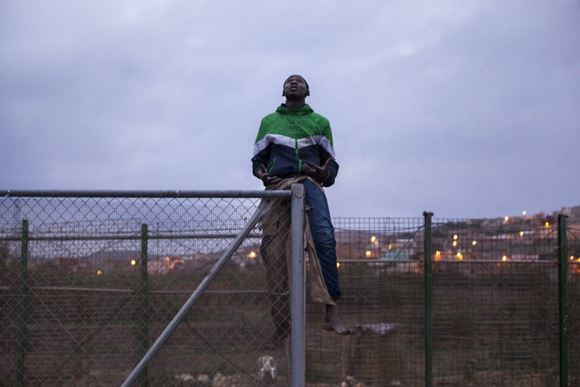 An injured migrant prays as he sits atop a border fence while Spanish police wait for him on the other side, in Melilla, Spain, Oct. 29, 2014.