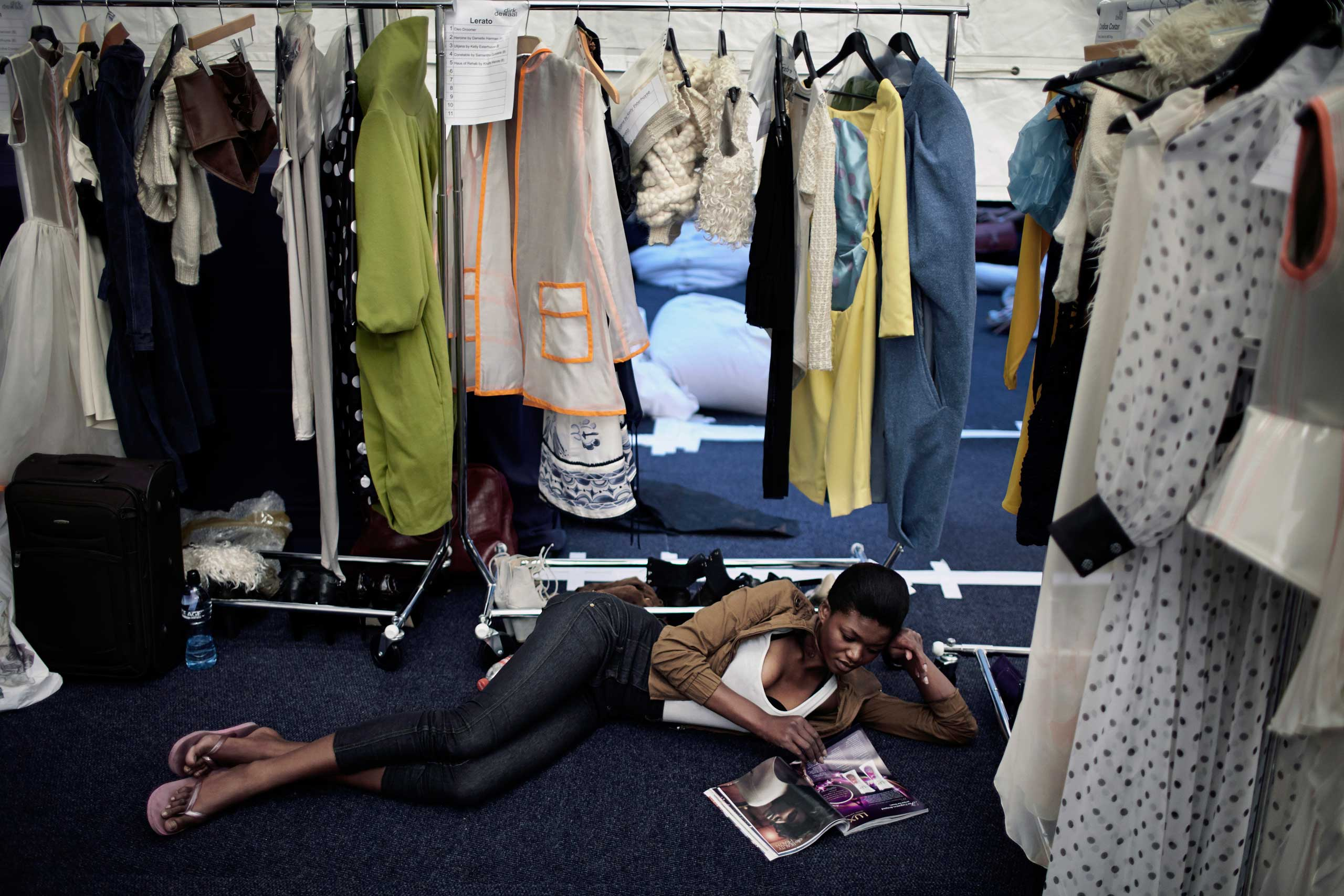 A models reads a fashion magazine backstage before a fashion show at South Africa Fashion Week on Sept. 22, 2011 held in Johannesburg, South Africa.
