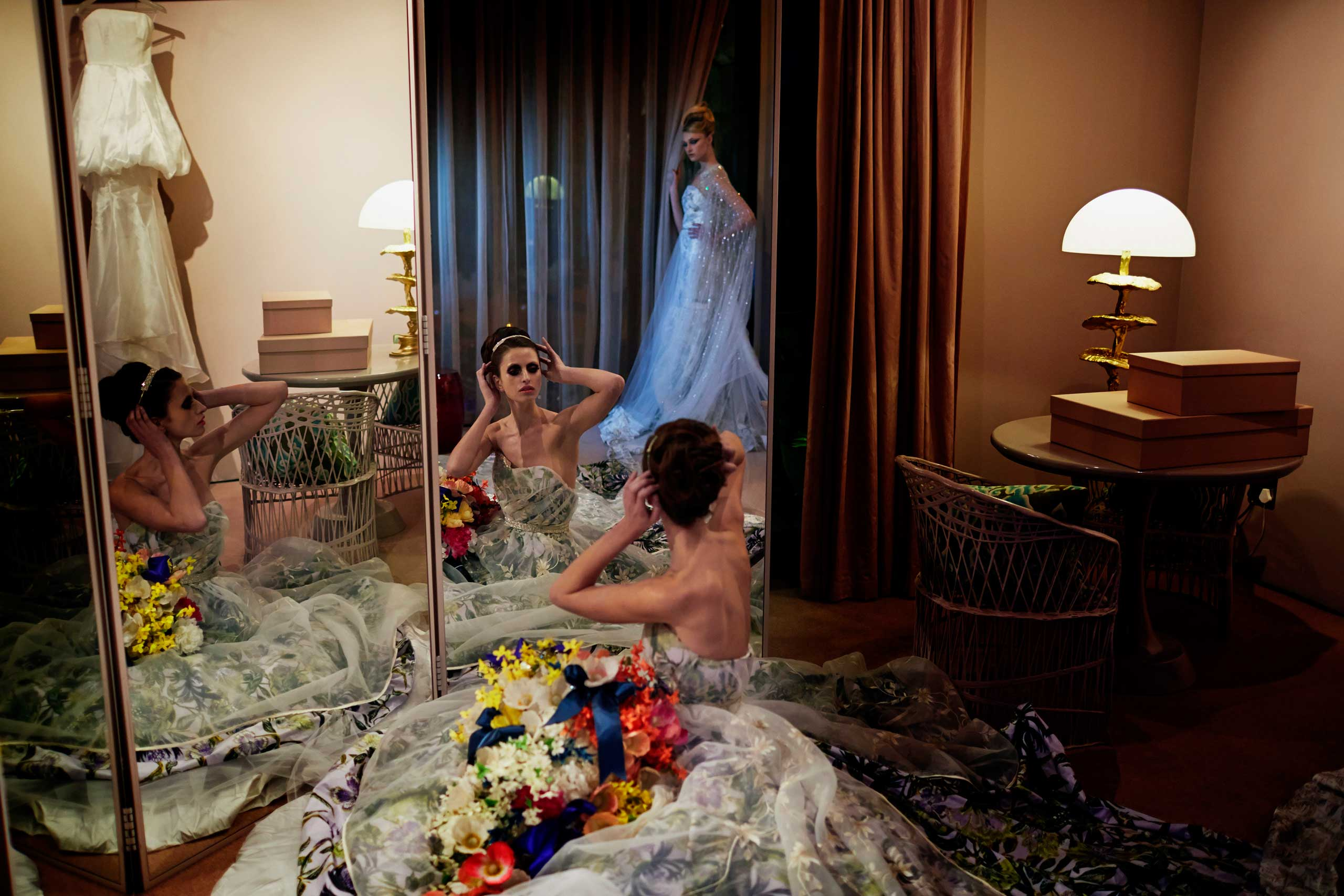Models pose in a wedding dressing room during an installation show at the new Klûk CGDT flagship store during Mercedes-Benz Fashion Week on July 26, 2014, in Cape Town, South Africa.
