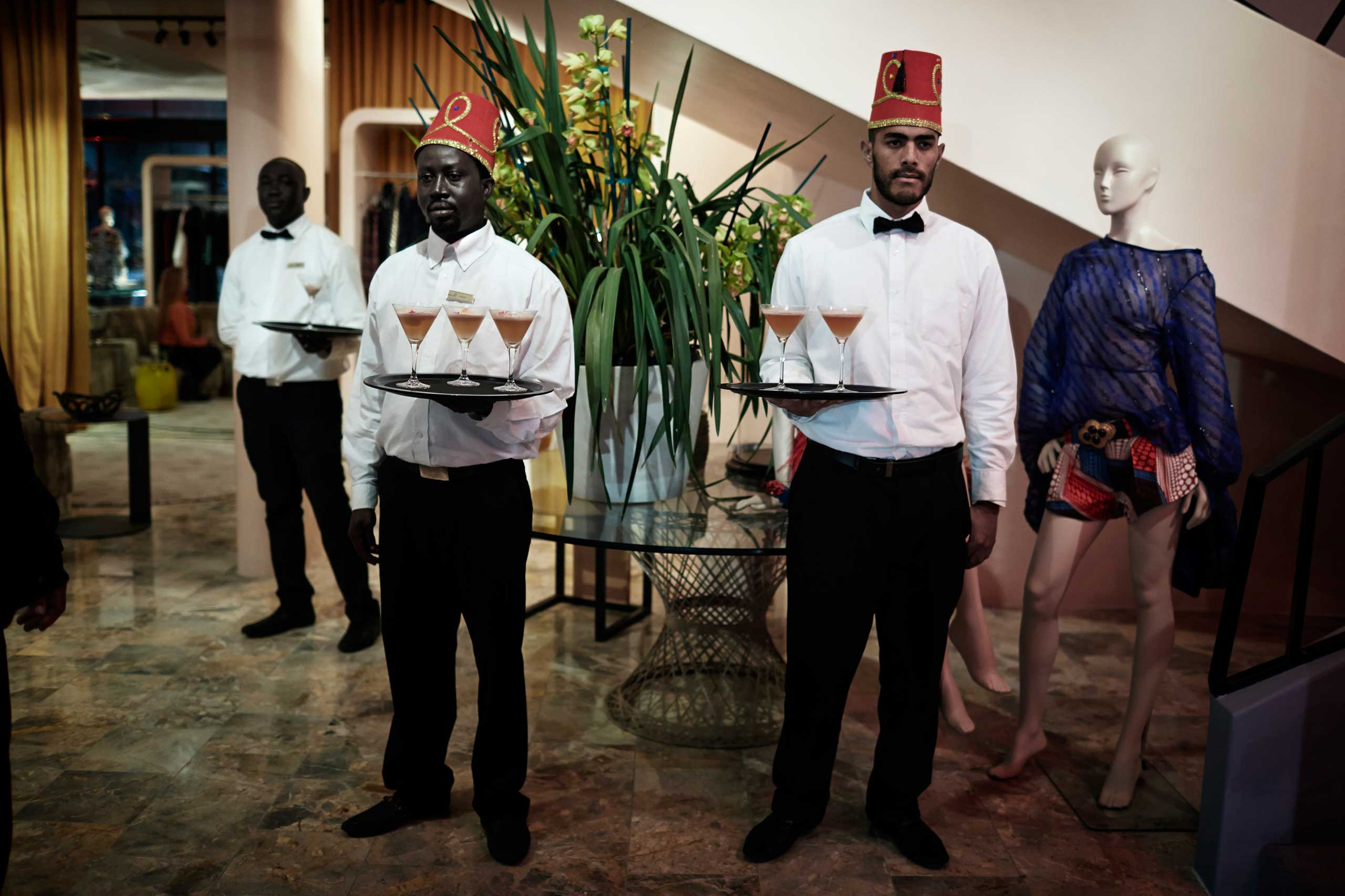 Waiters wait to serve drinks to guests before an installation show at the new Klûk CGDT flagship store during Mercedes-Benz Fashion Week on July 26, 2014, in Cape Town, South Africa.