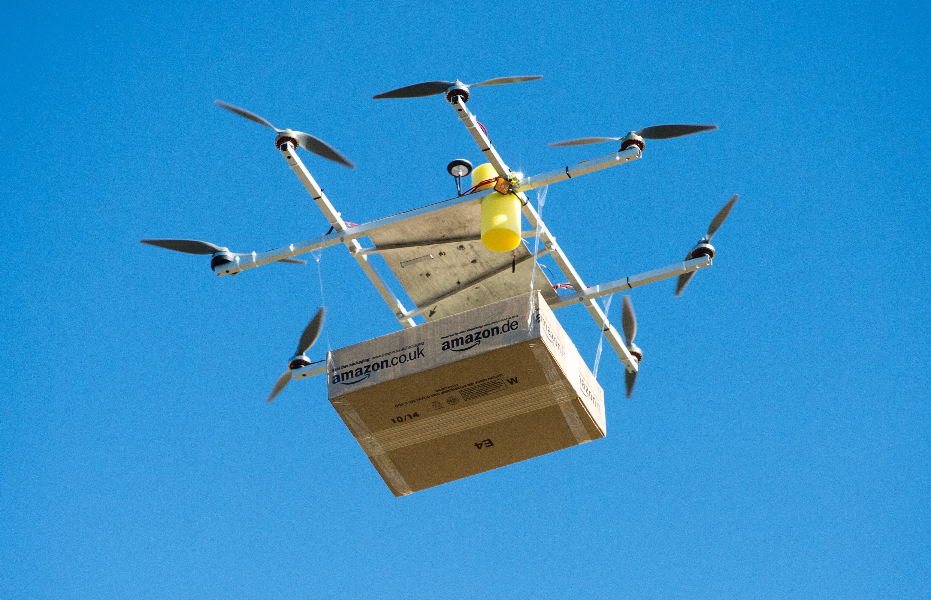 A drone with an Amazon package floats in front of the Amazon logistics center in Leipzig, Germany on Oct 28, 2014.