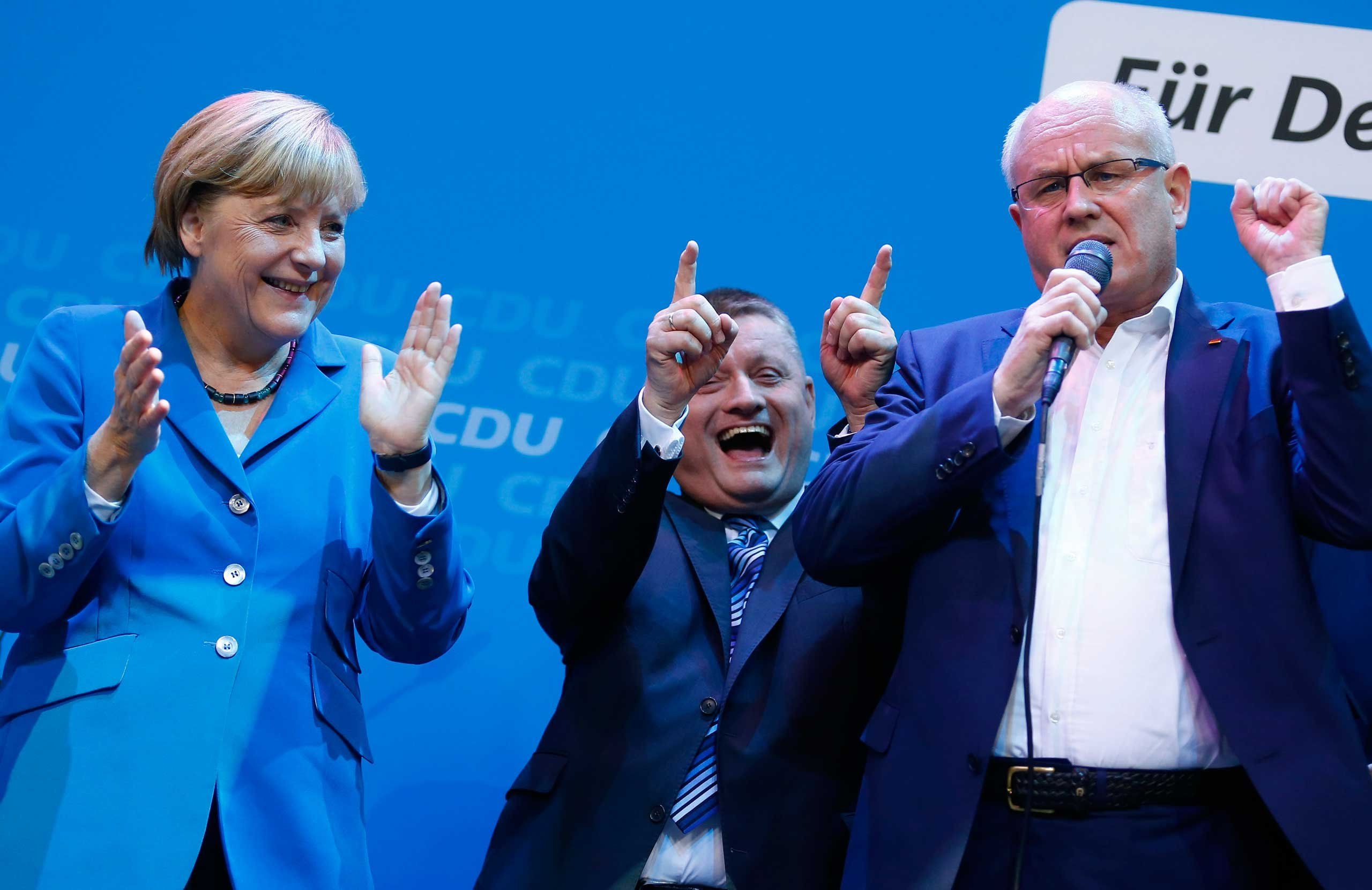 Leaders of the Christian Democratic Union sing with Chancellor Angela Merkel as they celebrate the exit polls in the German general election at the party headquarters in Berlin, Sept. 22, 2013.