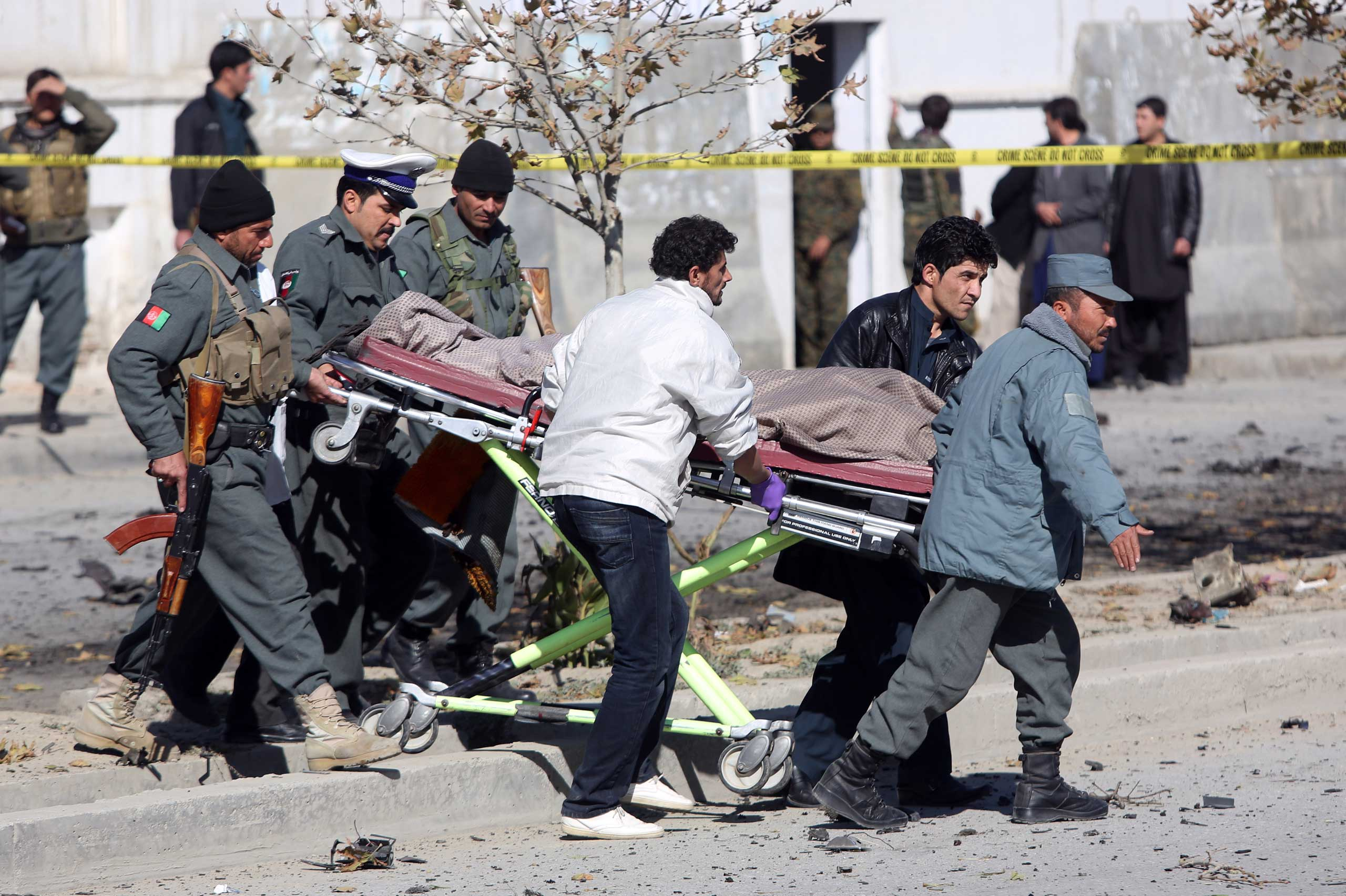 Afghan security forces carry the body of a civilian after a suicide attack in Kabul that targeted Shukria Barazkai, a prominent female member of Afghanistan's parliament, Nov. 16, 2014.