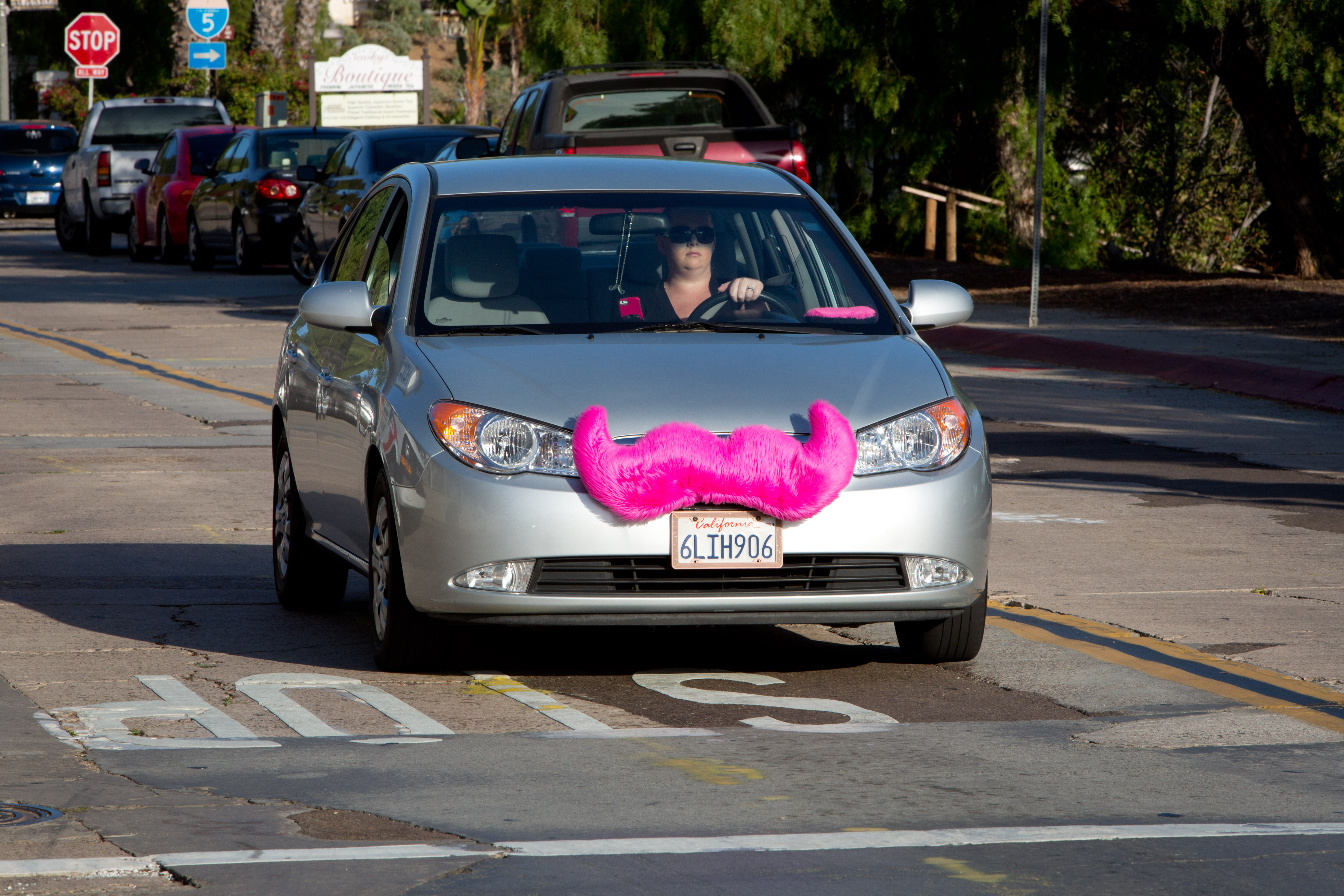 A woman is driving a car for the rideshare company Lyft with a fake jumbo pink mustache that attaches to the grille of the car, in June 2014.