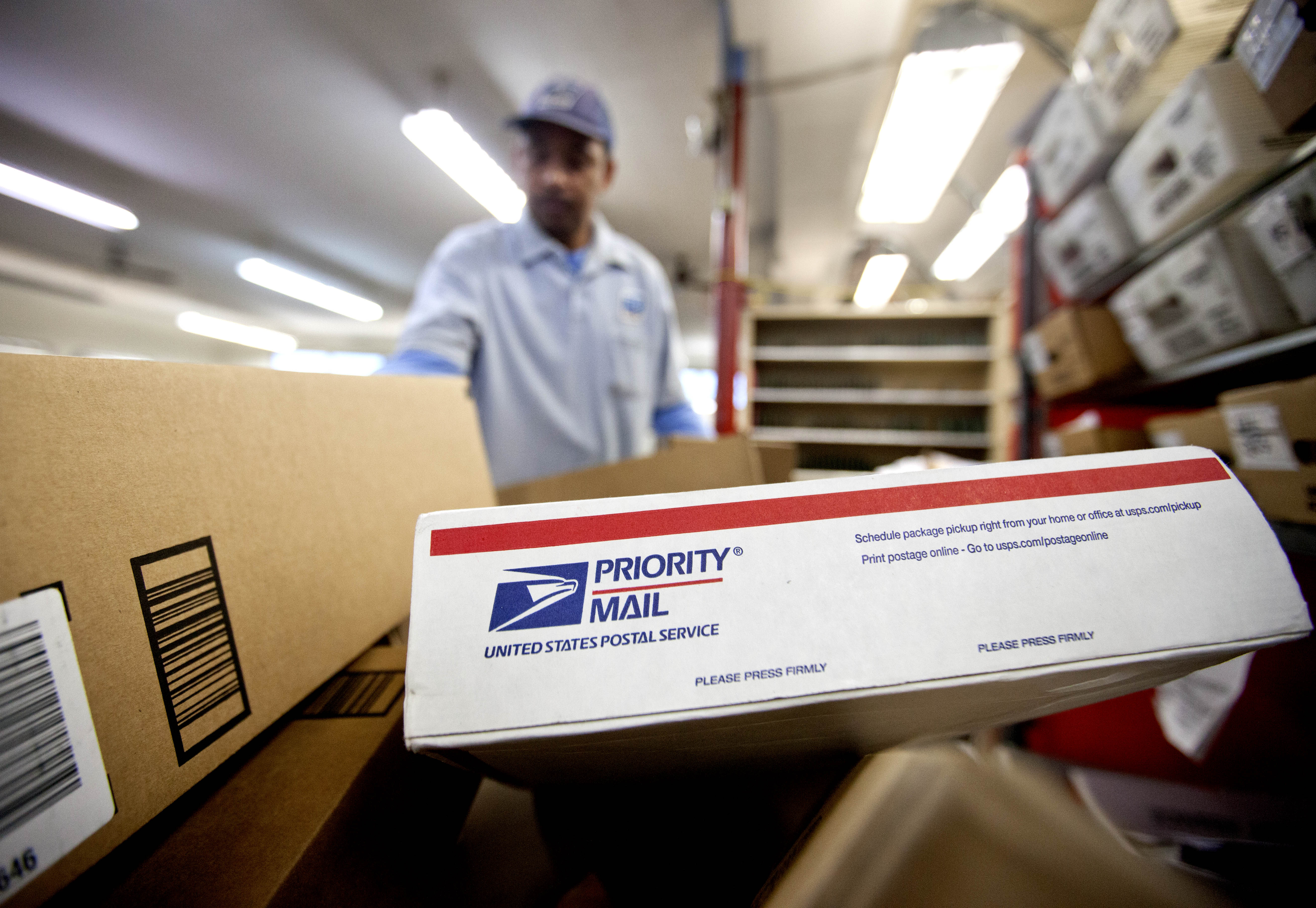 Packages wait to be sorted as a postal worker gathers mail to load into his truck before making a delivery run. The U.S. Postal Service recently announced that it will deliver packages seven days a week through Christmas Day.