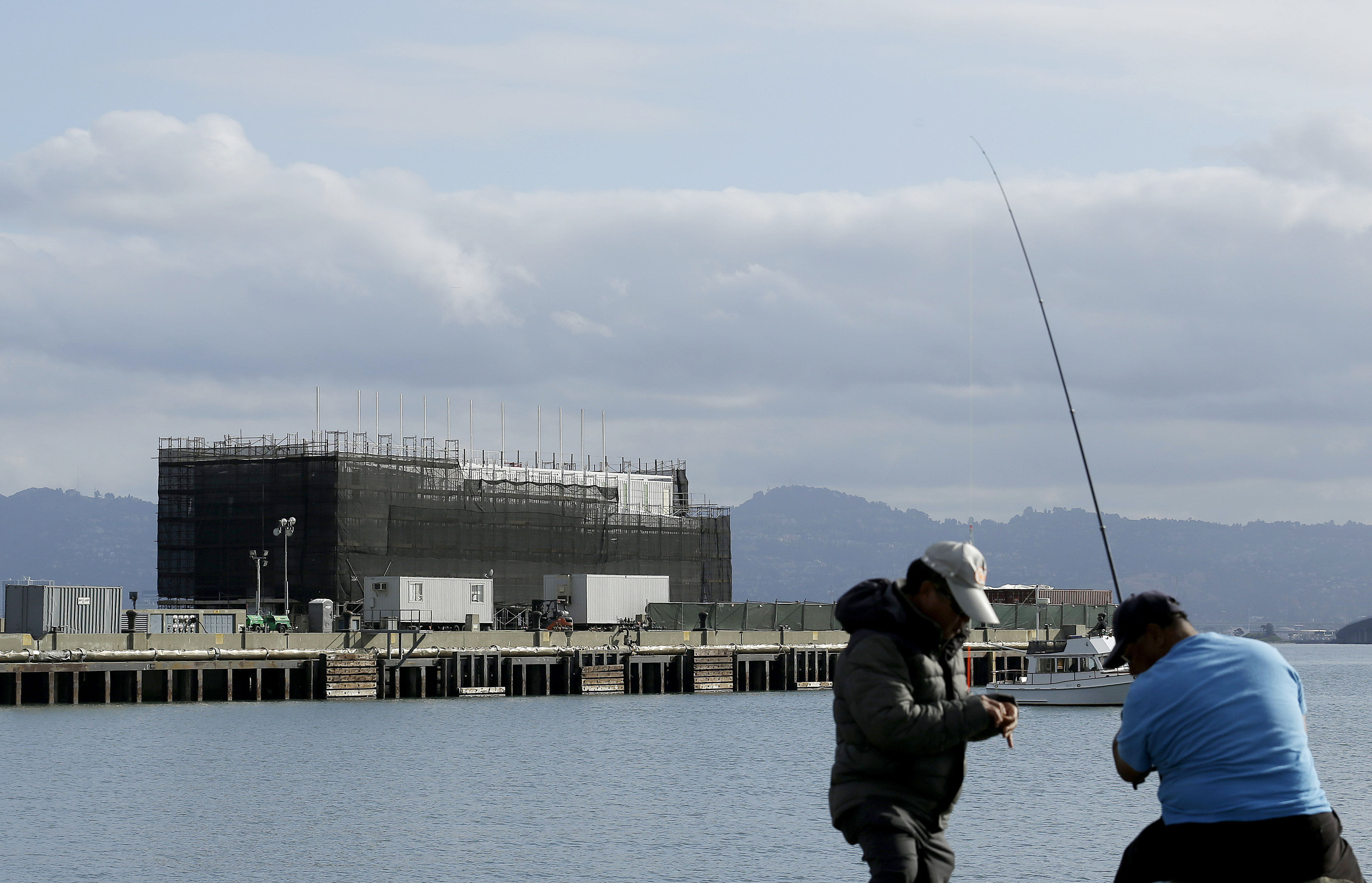 In this Tuesday, Oct. 29, 2013, file photo, two men fish in the water in front of a Google barge on Treasure Island in San Francisco. The barge portion of the Google barge mystery is only half the story.