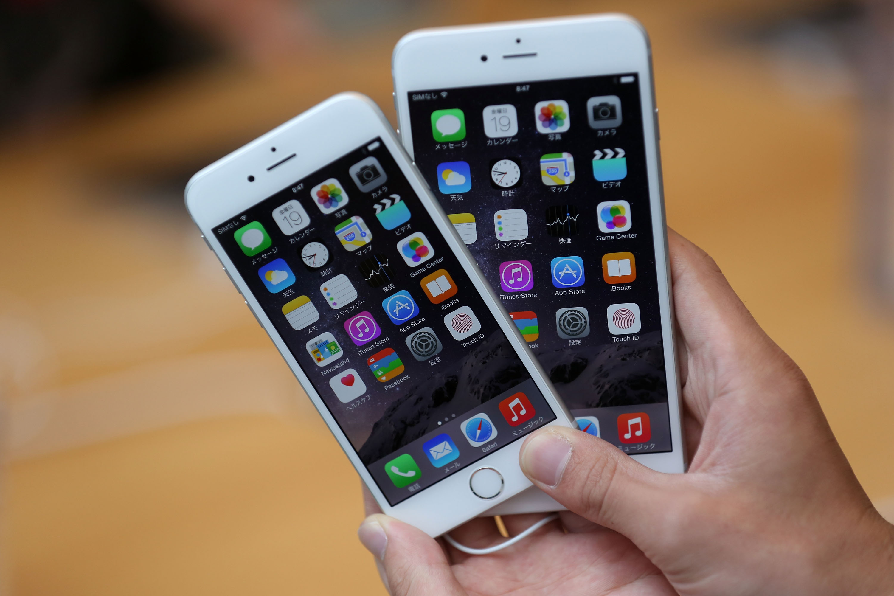 A member of the press compares the new iPhone models at the launch of the new Apple iPhone 6 and iPhone 6 plus at the Apple Omotesando store on September 19, 2014 in Tokyo, Japan.