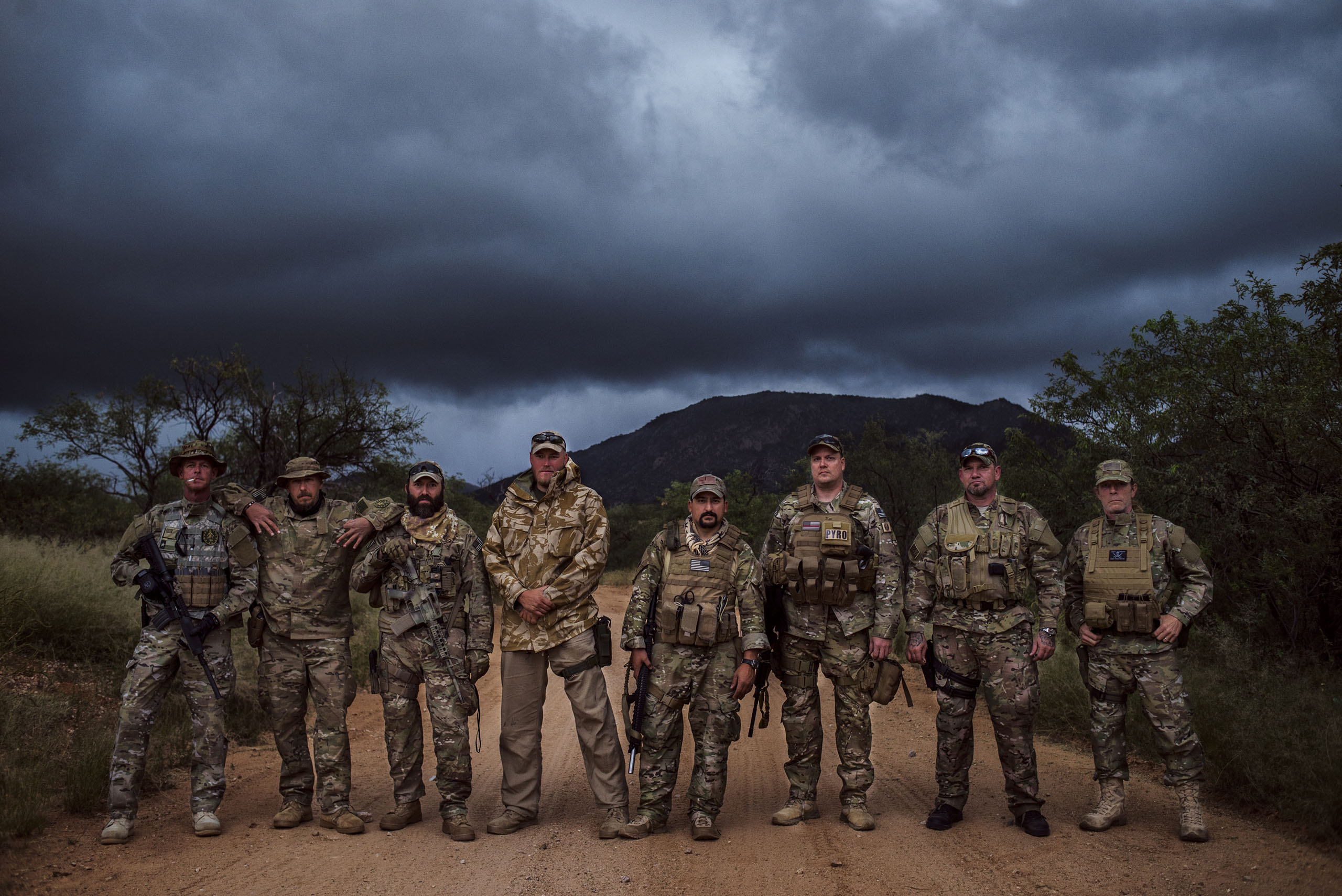From an Al Jazeera America post: Desert Hawks — Paramilitary veterans group stakes out US-Mexico borderlandsMembers of the Arizona Border Recon pause for a group photo. For some, this was their first time out with the team.  Sasabe, Arizona. Oct. 7, 2014.
