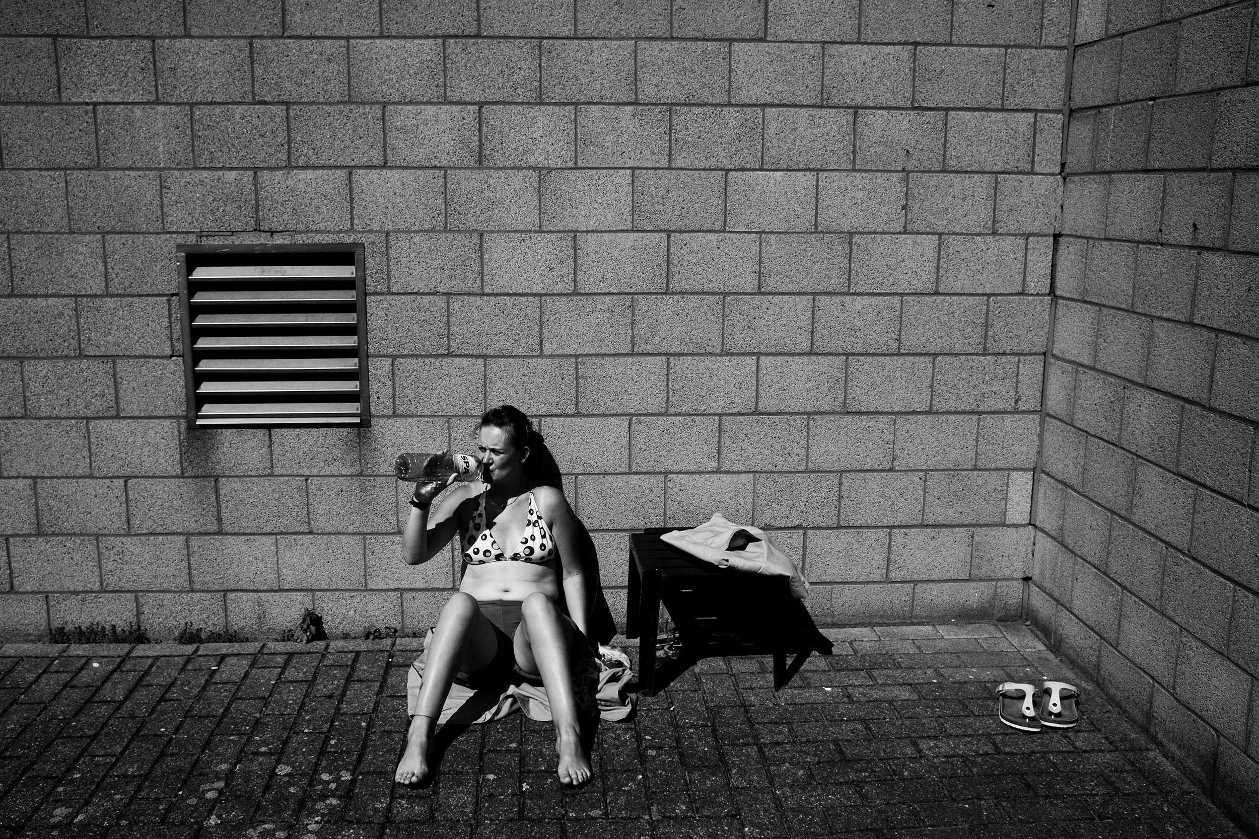 A female prisoner sunbathing at the women's prison in Berkendaele, Brussels. This courtyard is located next to a prison for men, whose cells offer a direct view on the women's courtyard. Some of the women enjoy mocking the men or exposing themselves to them. Brussels, Belgium. July 2011.