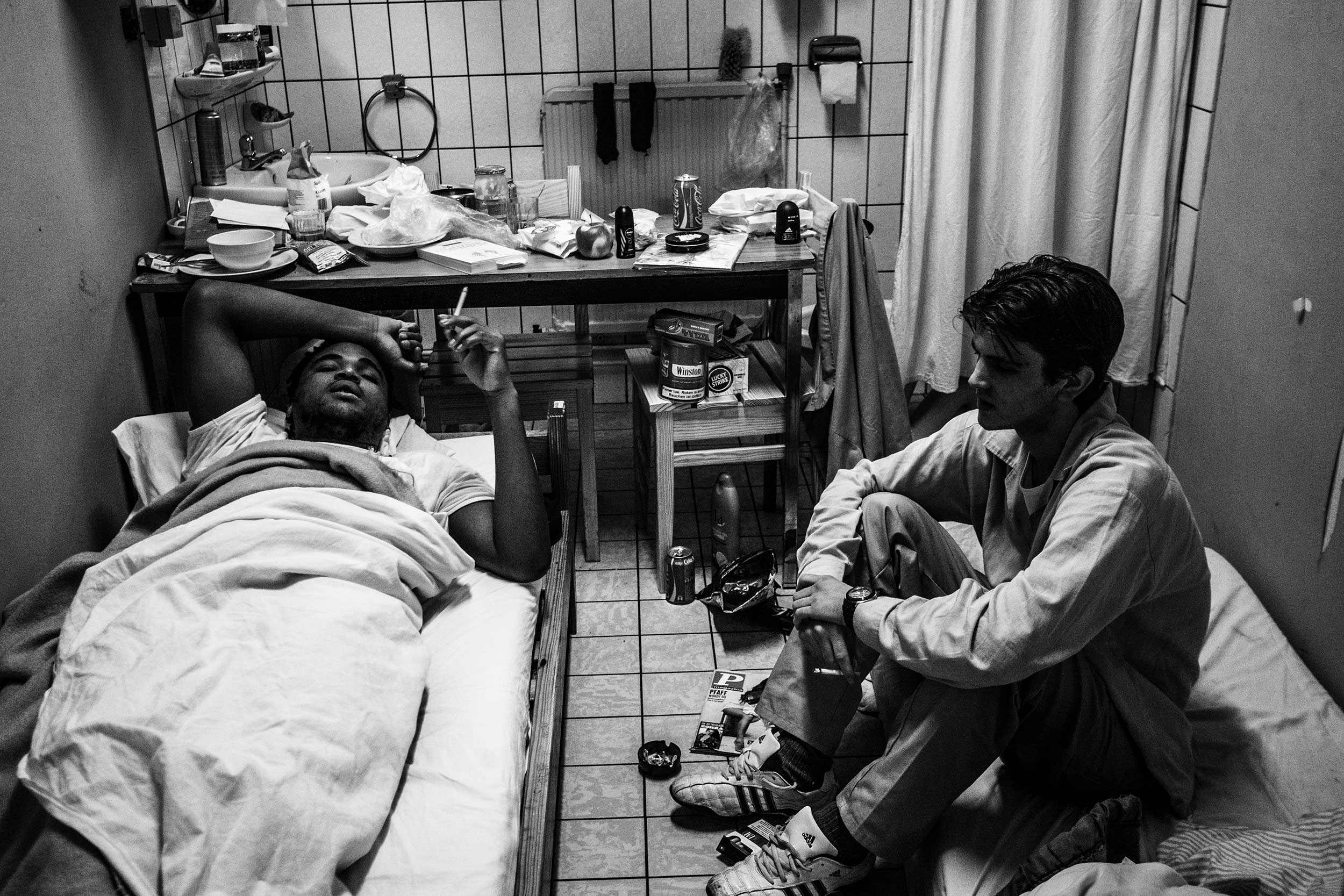 Two inmates are talking and smoking cigarettes in their cell. One of them sleeps on the floor due to overcrowding at the prison. A curtain hides the toilet. Ghent, Belgium. December 2013.
