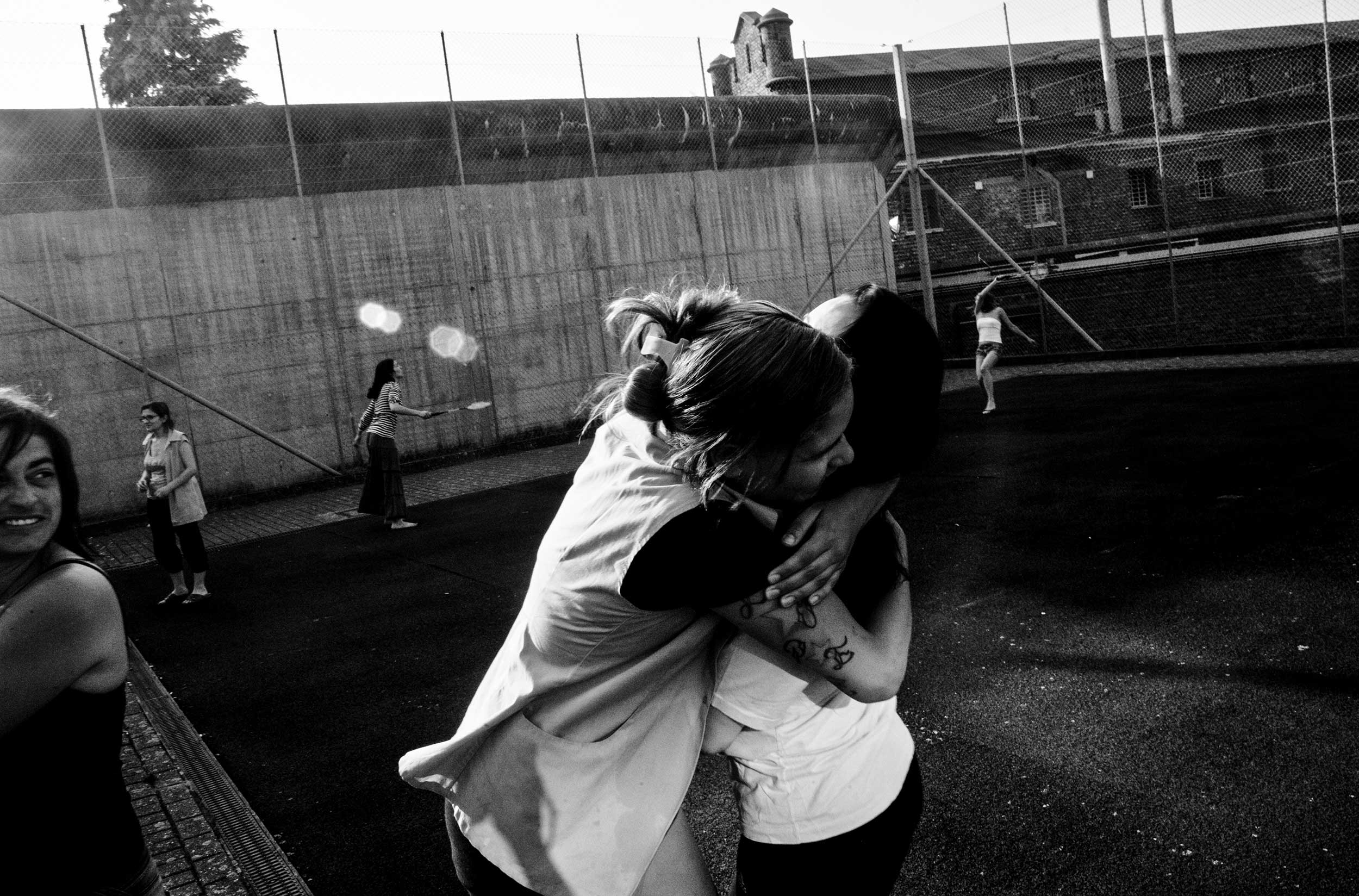 Two female prisoners hug during a badminton game in the courtyard of the prison for women in Berkendaele, Brussels, Belgium. July 2012.