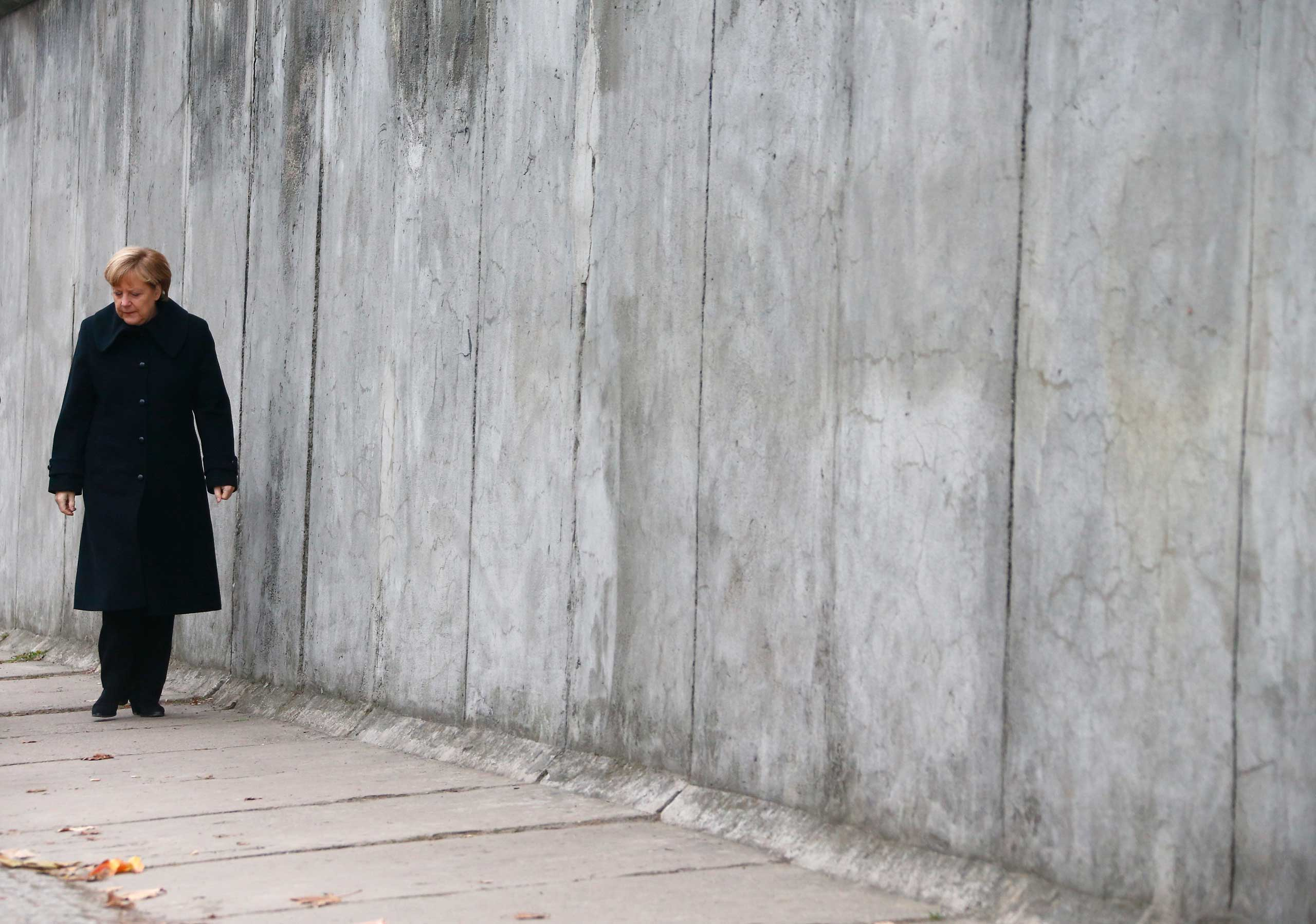 German Chancellor Angela Merkel walks along a section of the former Berlin Wall at the memorial in Bernauer Strasse, during a ceremony marking the 25th anniversary of the fall of the Berlin Wall, in Berlin on November 9, 2014.