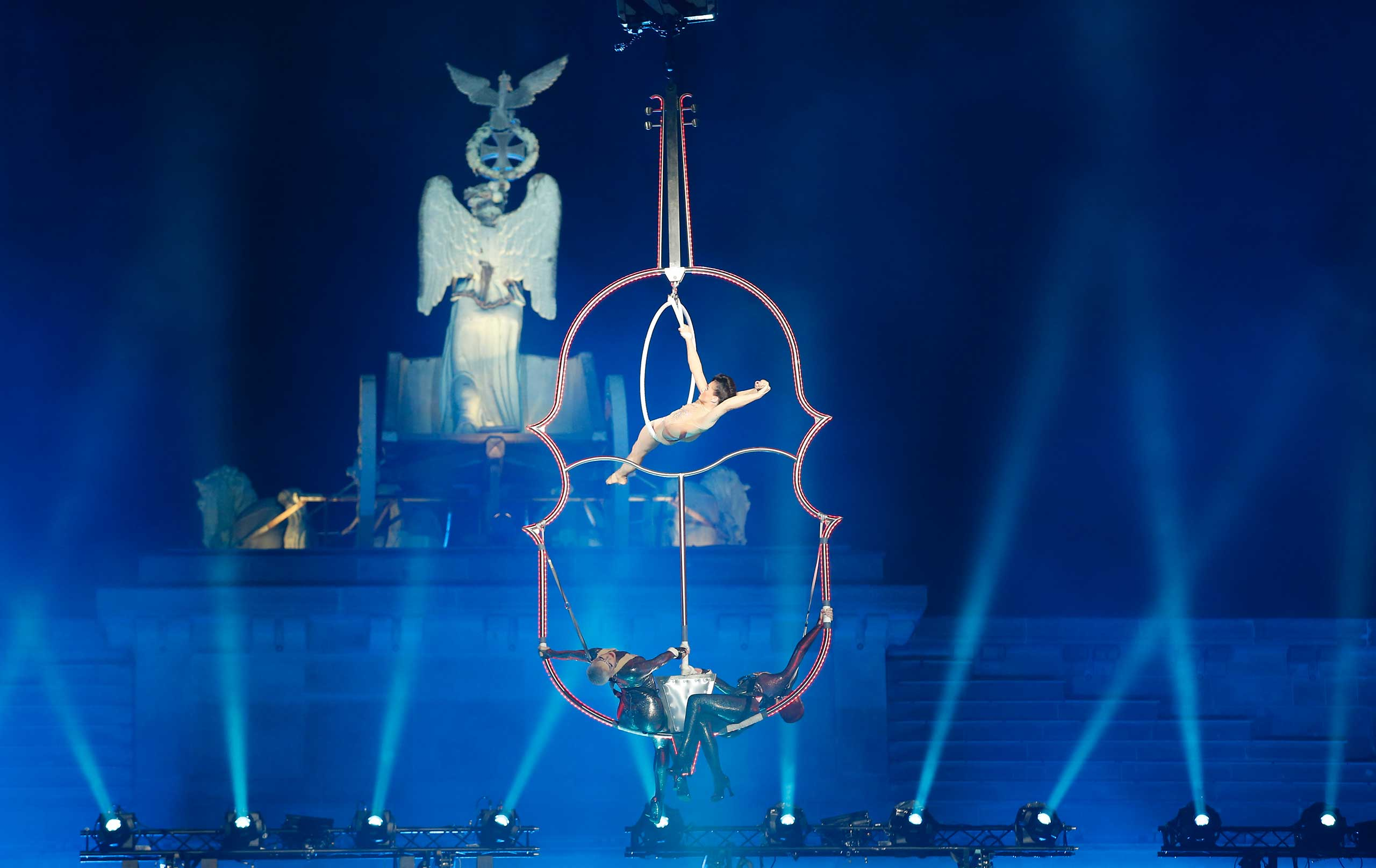 An acrobatic artist performs in front of the Quadriga on top of the Brandenburg Gate in Berlin, November 9, 2014.