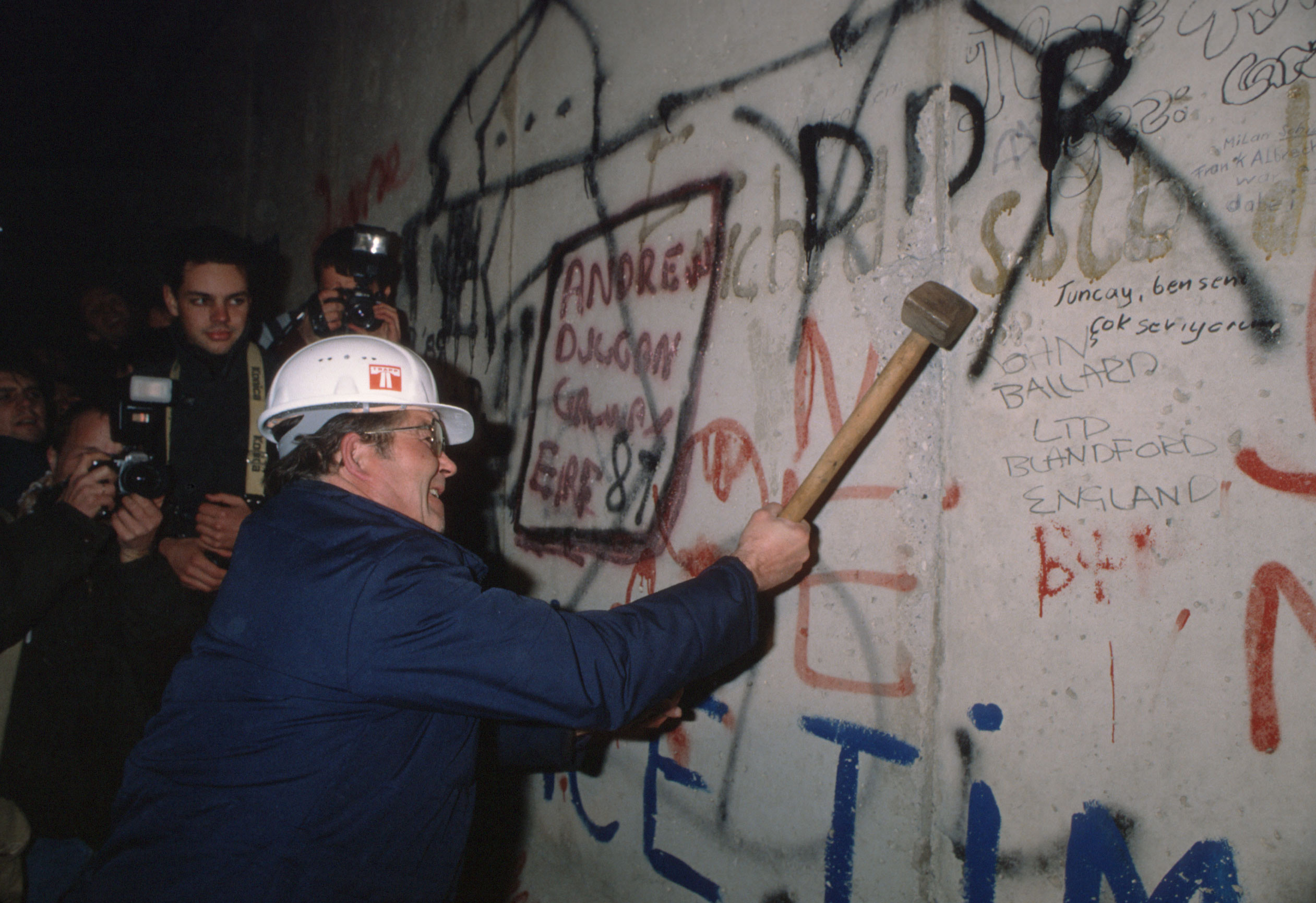 A man knocks out a piece of stone from the Berlin Wall after the border opened on Nov. 9, 1989, in Berlin.