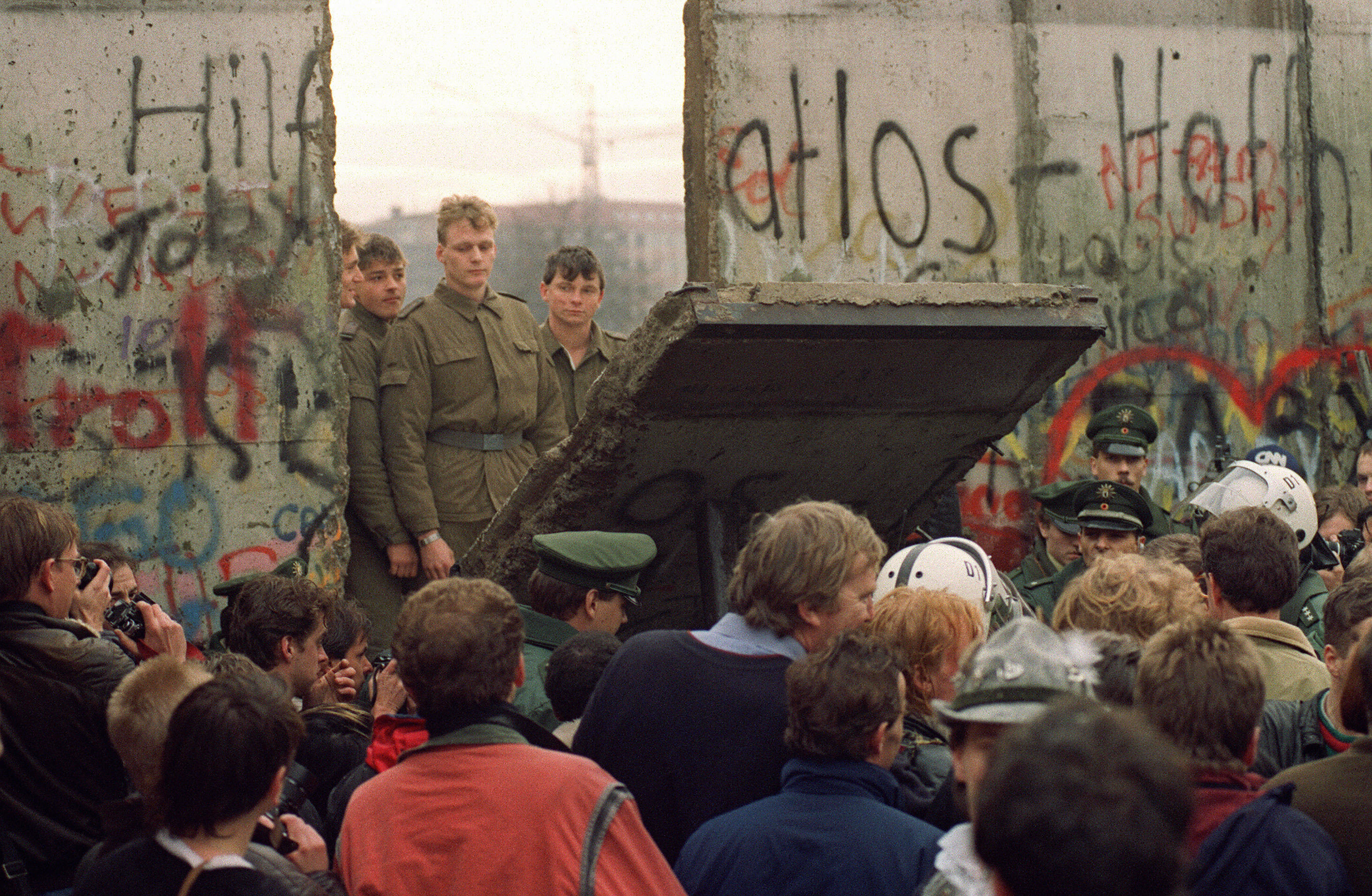 A crowd in front of the Berlin Wall on Nov. 11, 1989 watches border guards demolish a section of the wall in order to open a new crossing point between East and West Berlin in Germany.