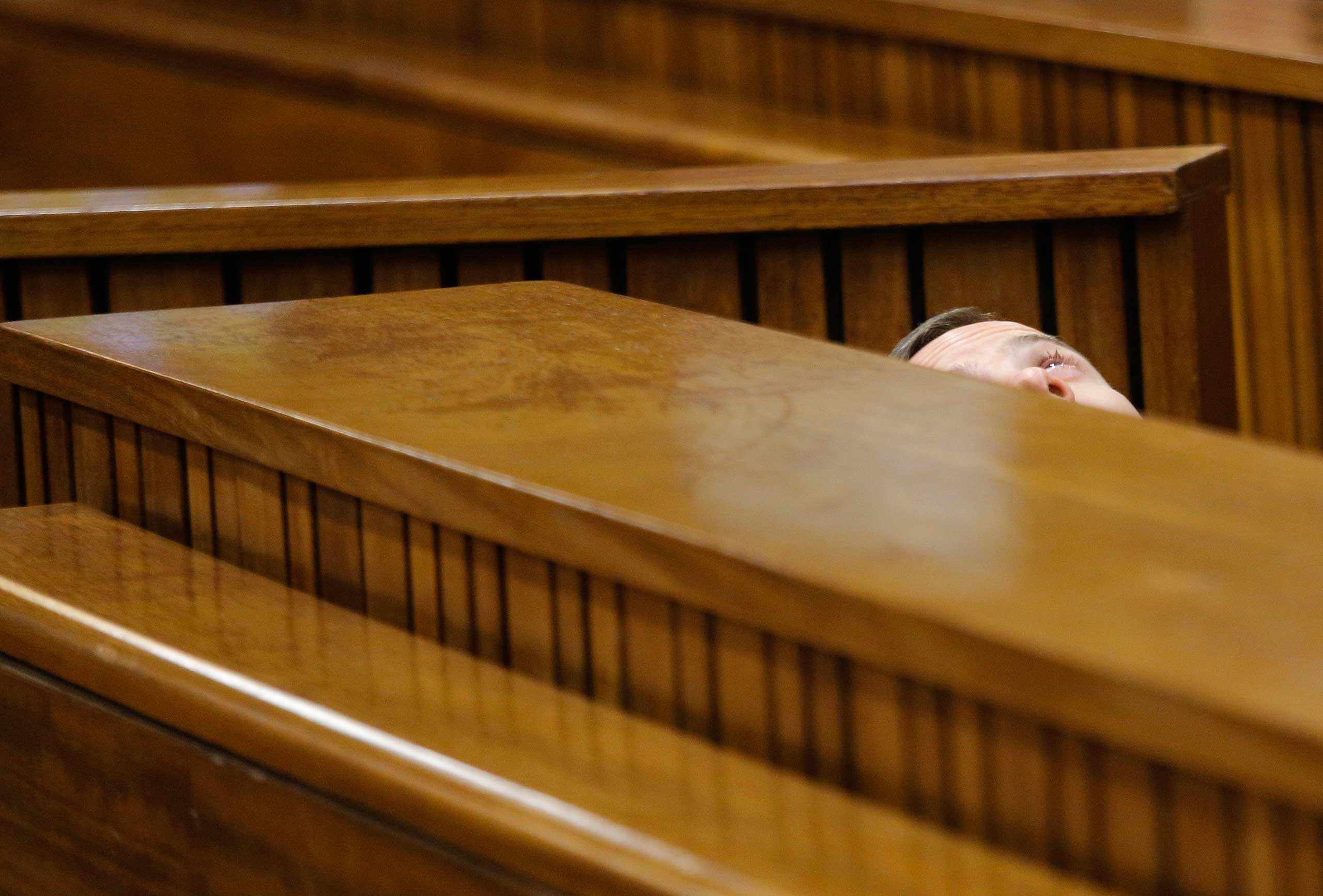 South African Paralympic athlete Oscar Pistorius is seen leaning back after applying eye drops as he prepares himself for another day in the dock during his ongoing murder trial in Pretoria, South Africa, March 14, 2014.