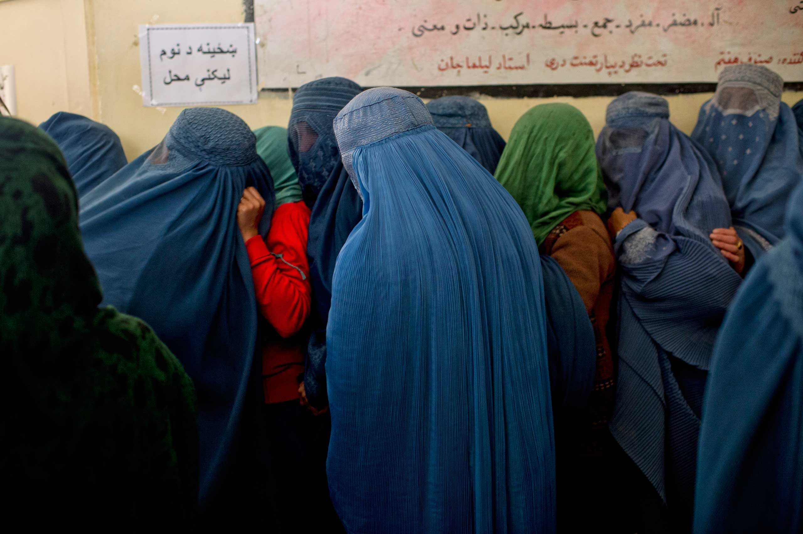 Afghans line up to register to vote for Presidential elections at a center run by the Afghan Independent Electoral Commission in Shah Shaheed, Kabul, Afghanistan, March 25, 2014.