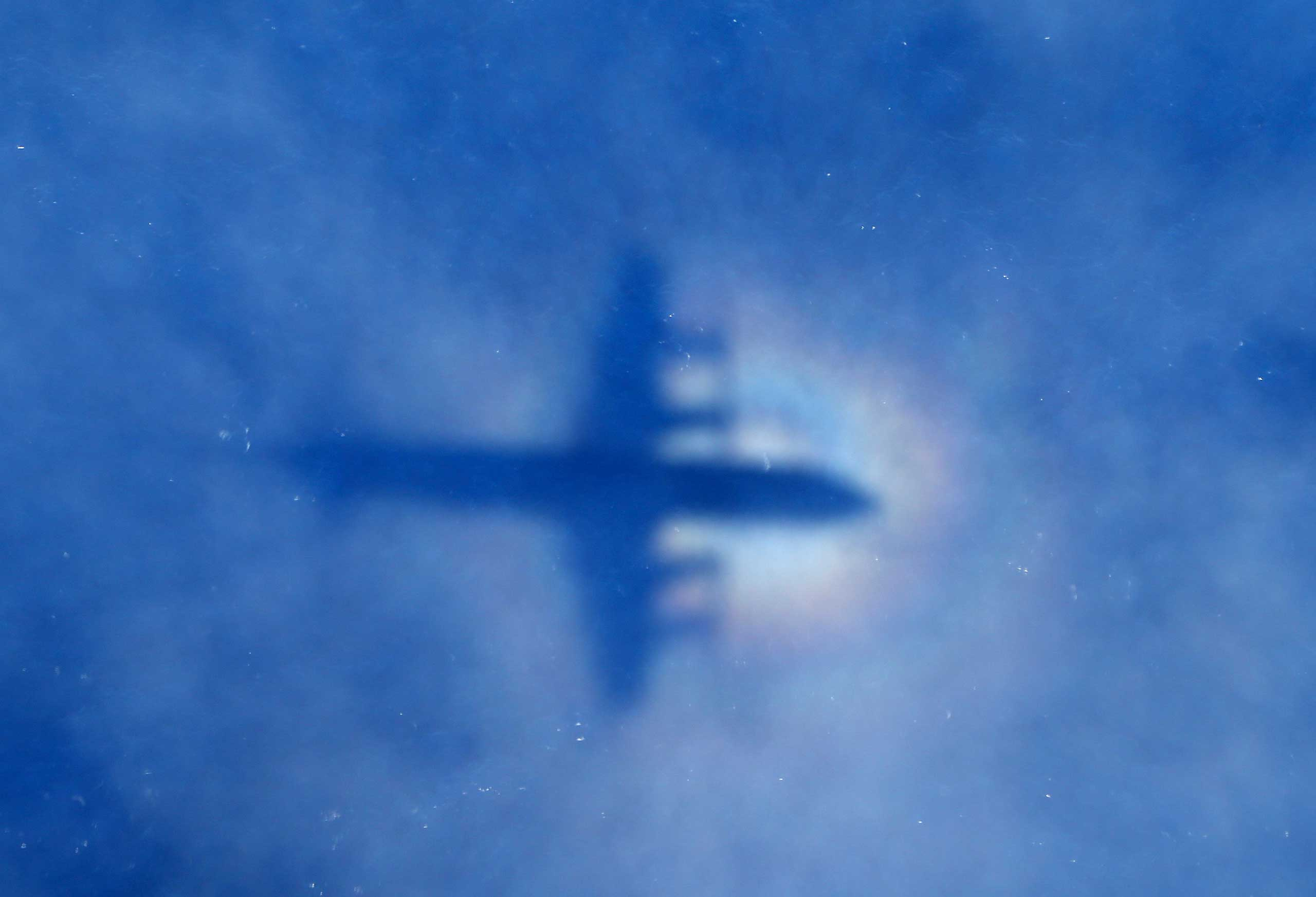 A shadow of a Royal New Zealand Air Force P3 Orion aircraft is seen on low cloud cover while it searches for missing Malaysia Airlines Flight MH370 in Perth, Australia, March 31, 2014.