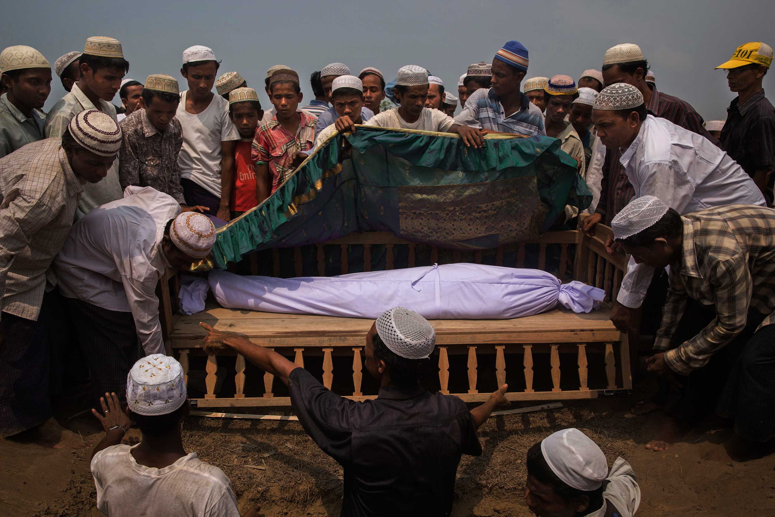 The body of Nur Husain, who died after suffering from a respiratory condition, is buried near his home in a camp near Sittwe, Myanmar. The Rohingya are a Muslim minority persecuted by Myanmar's Buddhist-led government, April 20, 2014.