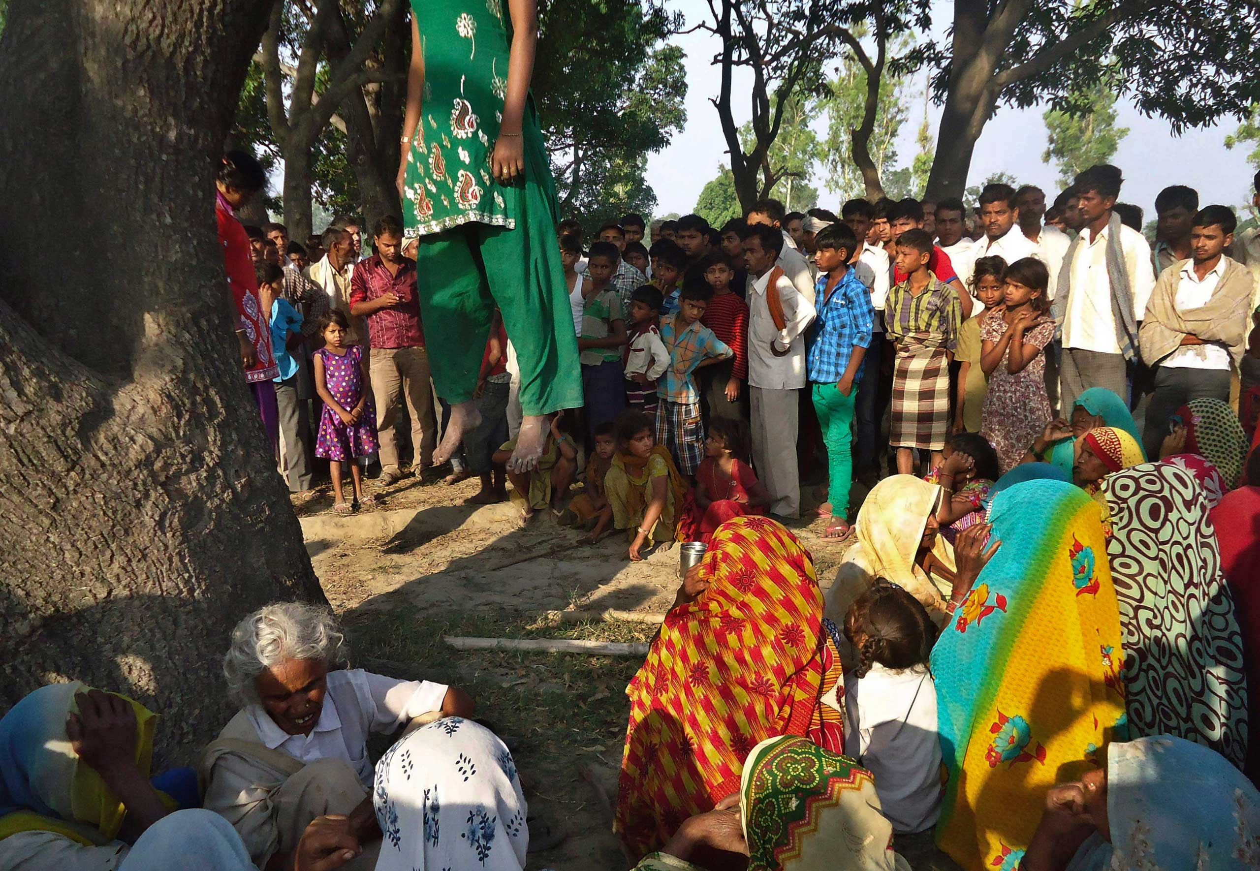 Indian villagers gather around the bodies of two teenage sisters hanging from a tree in Katra village in Uttar Pradesh state, India. The teenage sisters in rural India were raped and killed by attackers who hung their bodies from a mango tree, May 28, 2014.