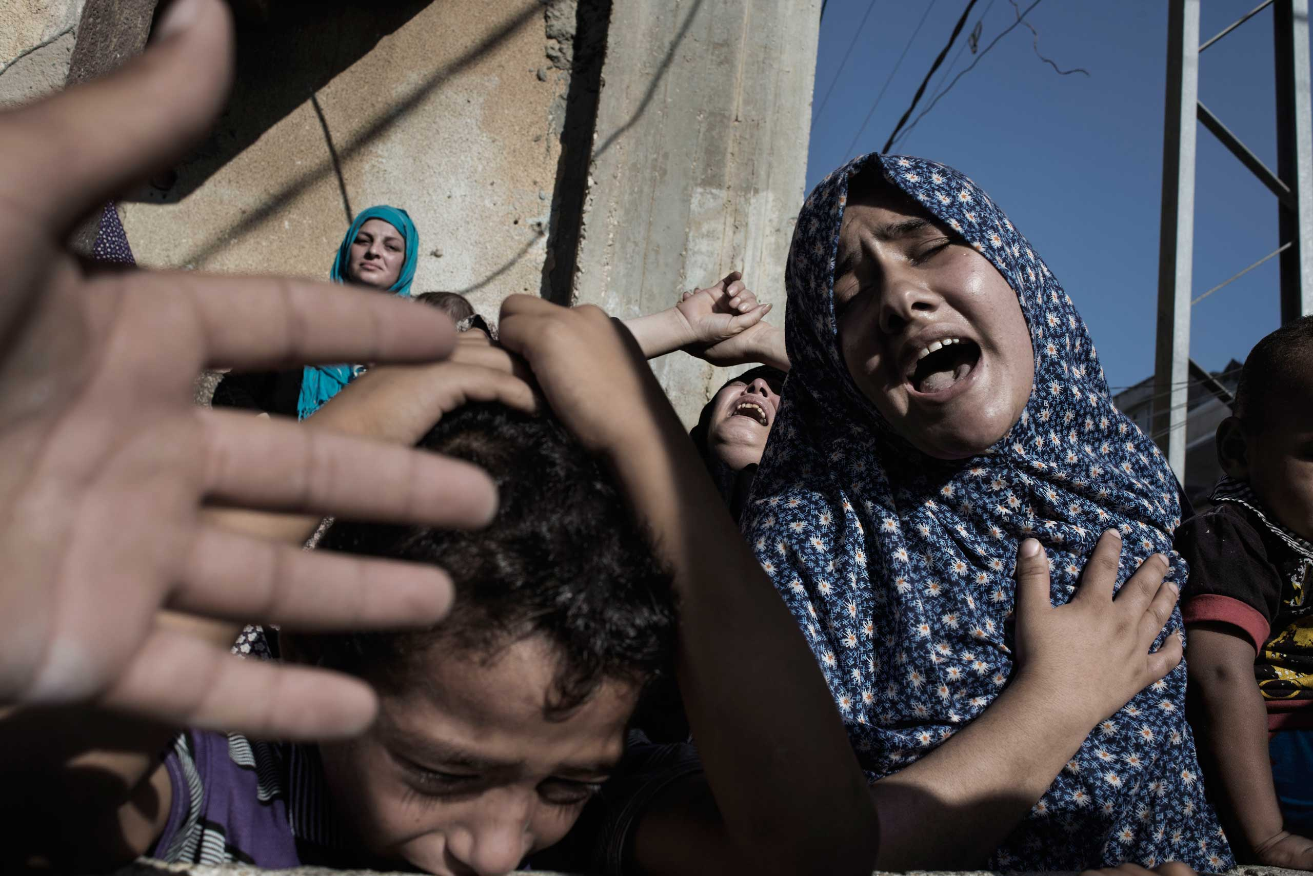 Relatives of four boys, all from the Bakr family, killed by Israeli naval bombardment, mourn during their funeral in Gaza City,  July 16, 2014.