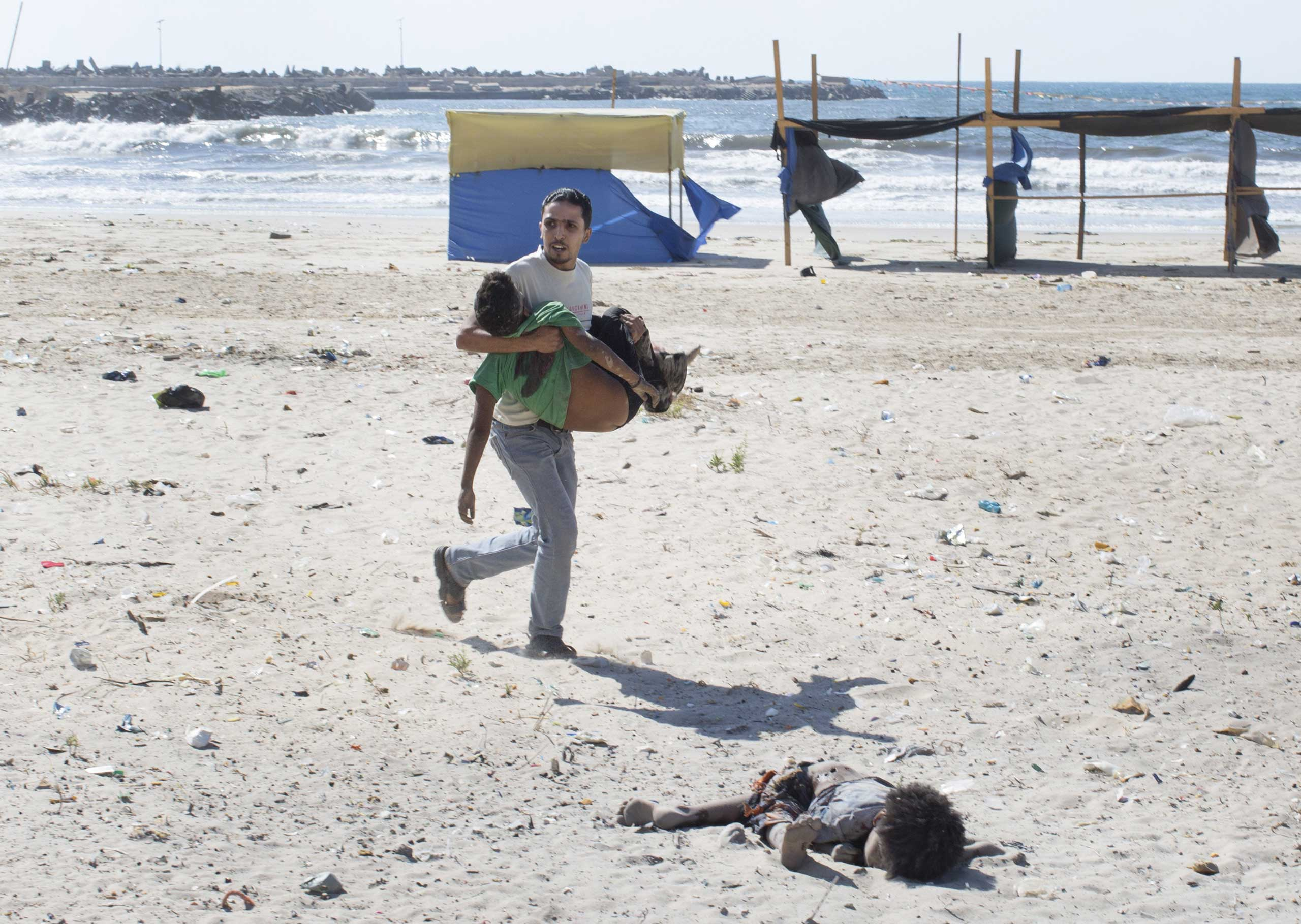 A man carries a child as another lies dead after two explosions on a beach in Gaza,  July 16, 2014.