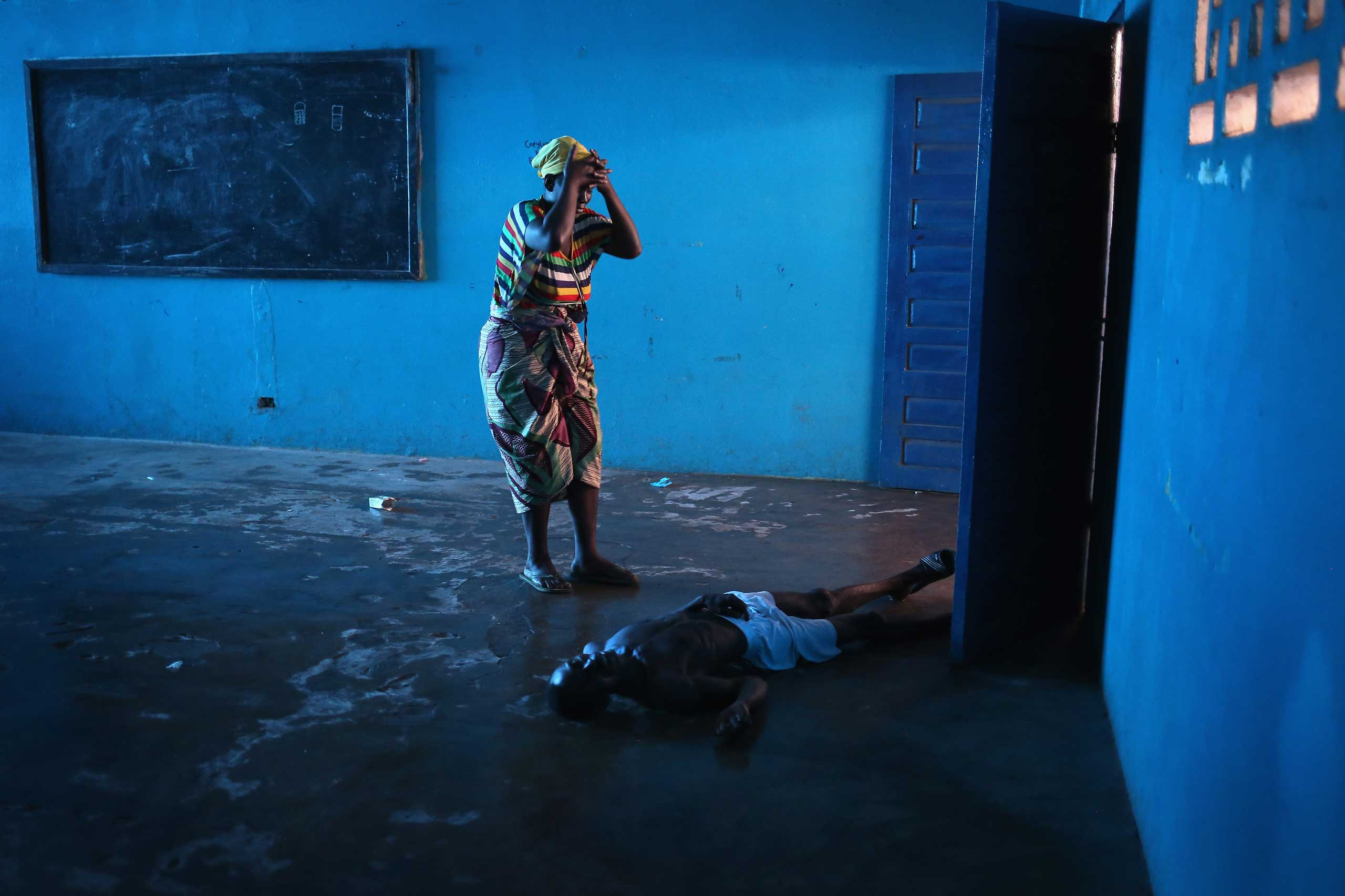 Umu Fambulle stands over her husband Ibrahim after he staggered and fell knocking him unconscious, in an Ebola ward in Monrovia, Liberia., Aug. 15, 2014.