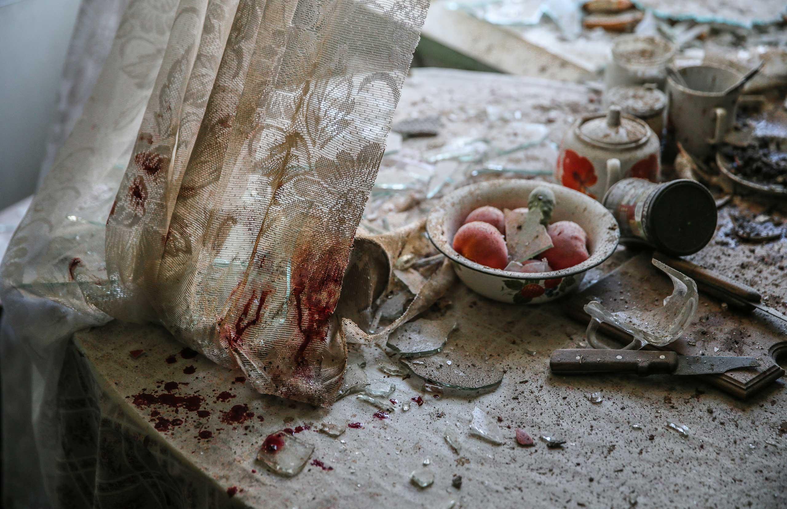 Damaged goods lie in a damaged kitchen in downtown Donetsk, Ukraine, Aug. 26, 2014.