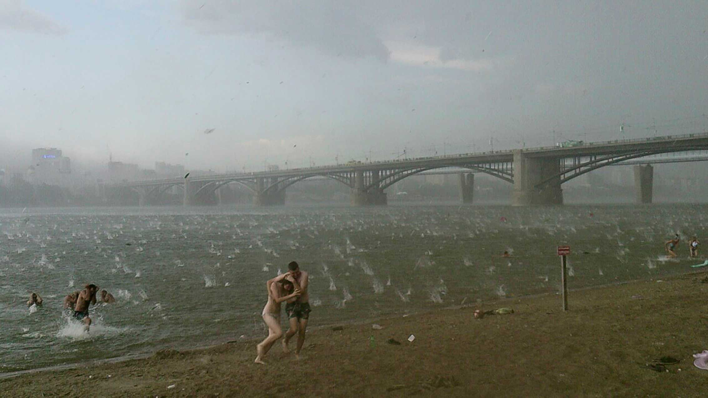 People run to shelter from hailstorm on the beach at Ob River, Novosibirsk, Russia, July 12, 2014.