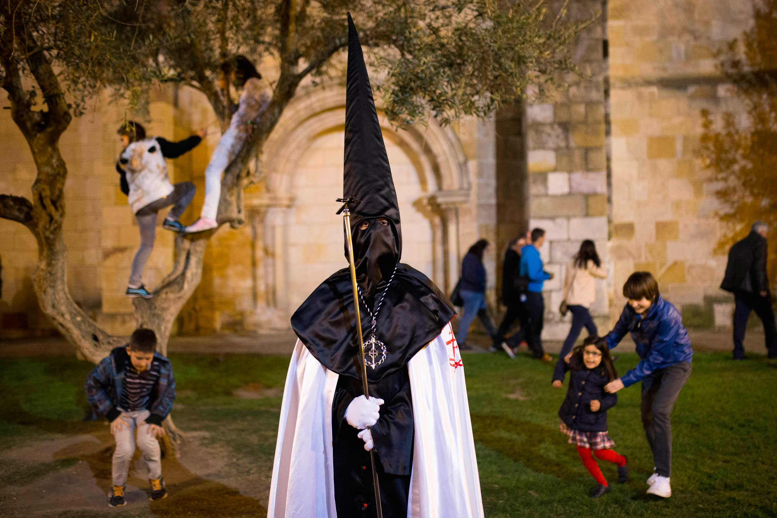 Children play in the background as a penitent watches a march in Zamora, Spain, April 14, 2014.