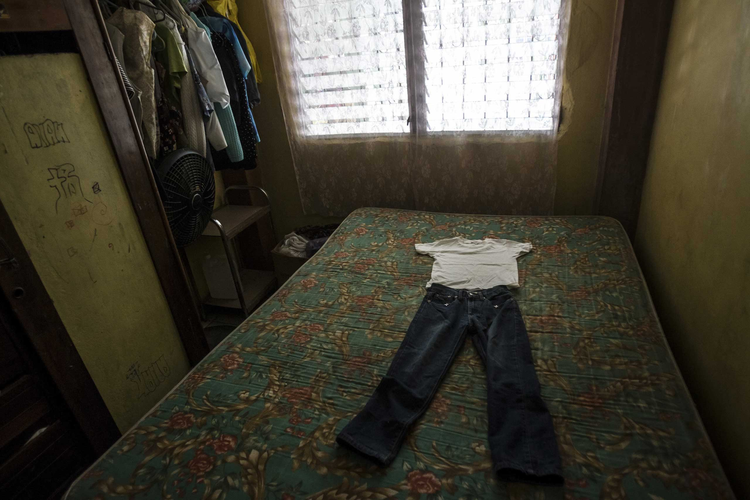 Clothes laid out on a bed for seven-year-old Kenneth Castellanos, whom police say was tortured to death by gang members in San Pedro Sula, Honduras, May 23, 2014.