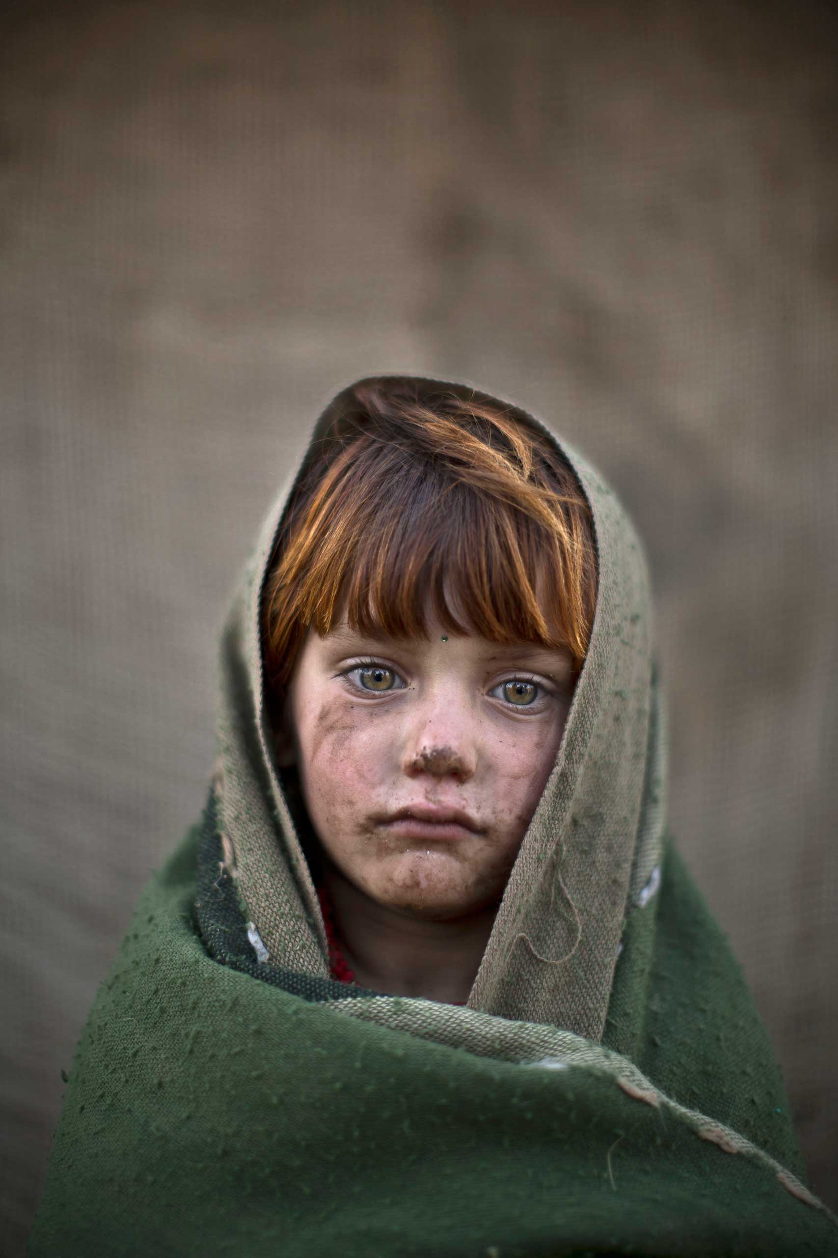 An Afghan refugee girl, laiba Hazrat, 6, poses for a picture, while playing with other children in a slum on the outskirts of Islamabad, Pakistan. Jan. 24, 2014.