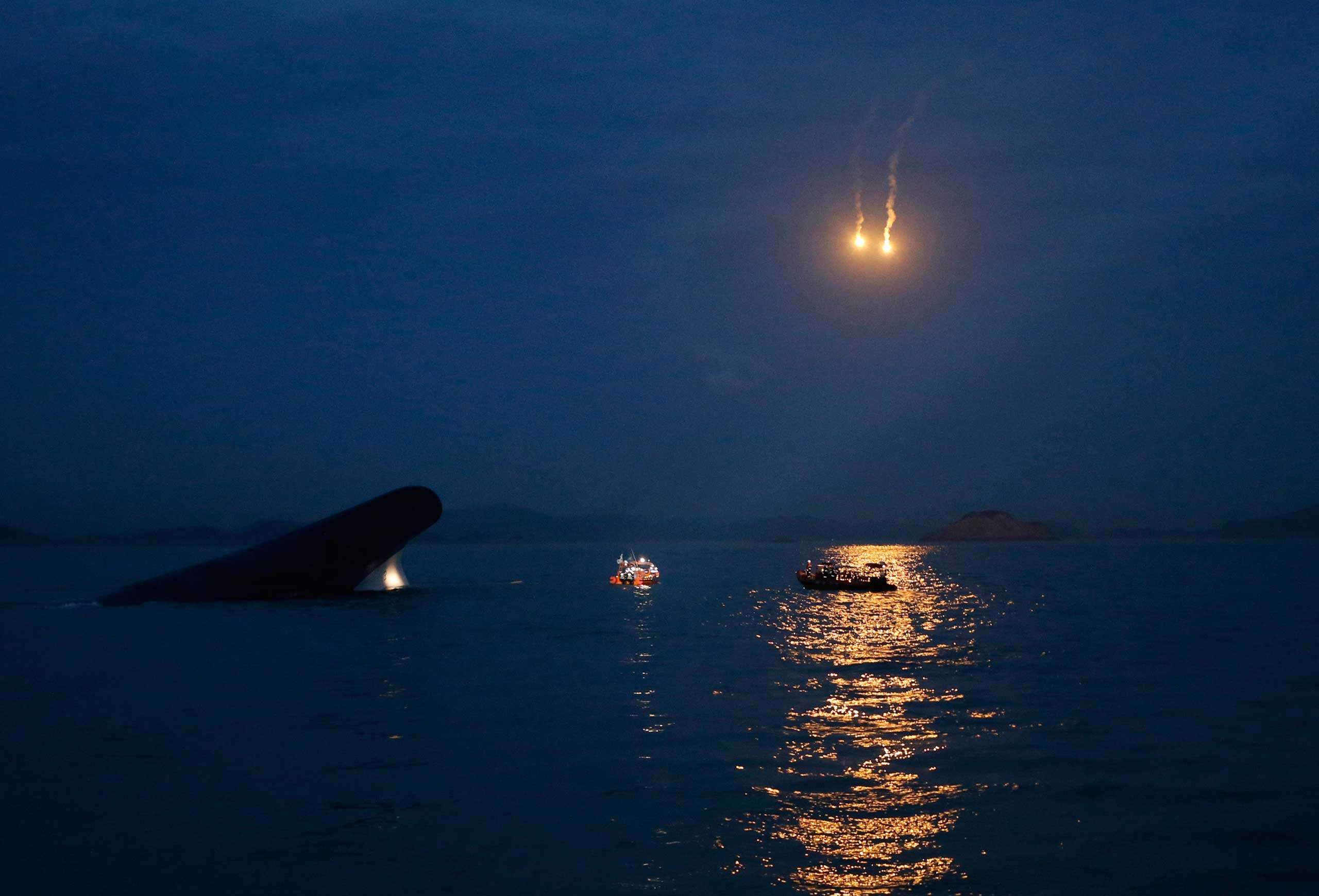 The South Korean ferry  Sewol  is seen sinking in the sea off Jindo, South Korea as lighting flares are released for a night search, April 16, 2014.