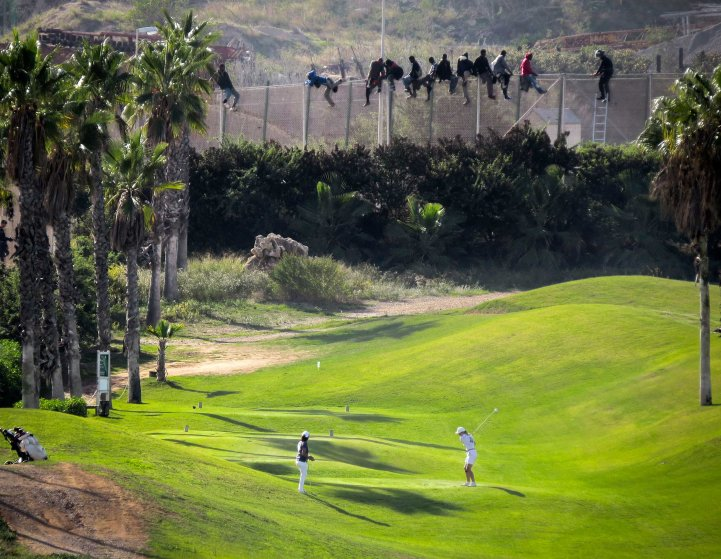 A golfer hits a tee shot as African migrants sit atop a border fence during an attempt to cross into Spanish territories between Morocco and Spain's north African enclave of Melilla, Oct. 22, 2014.