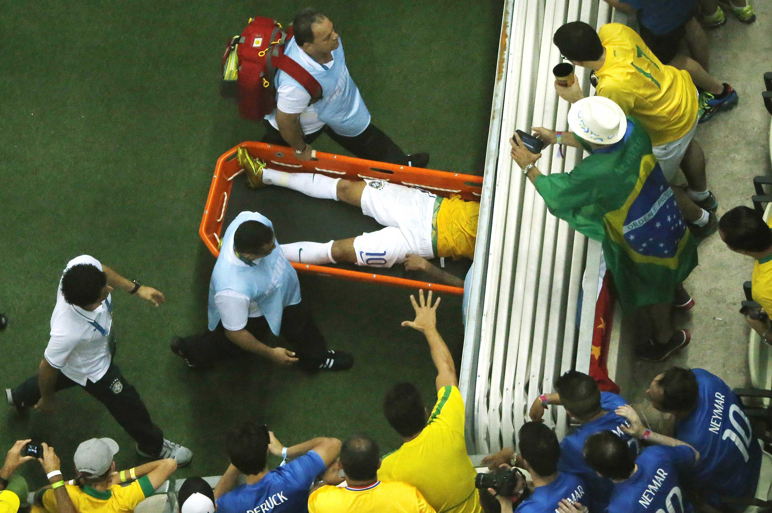 Fans react as Brazil's forward Neymar is carried off the pitch on a stretcher after being injured during the quarter-final football match between Brazil and Colombia at the Castelao Stadium in Fortaleza during the 2014 FIFA World Cup,  July 4, 2014.