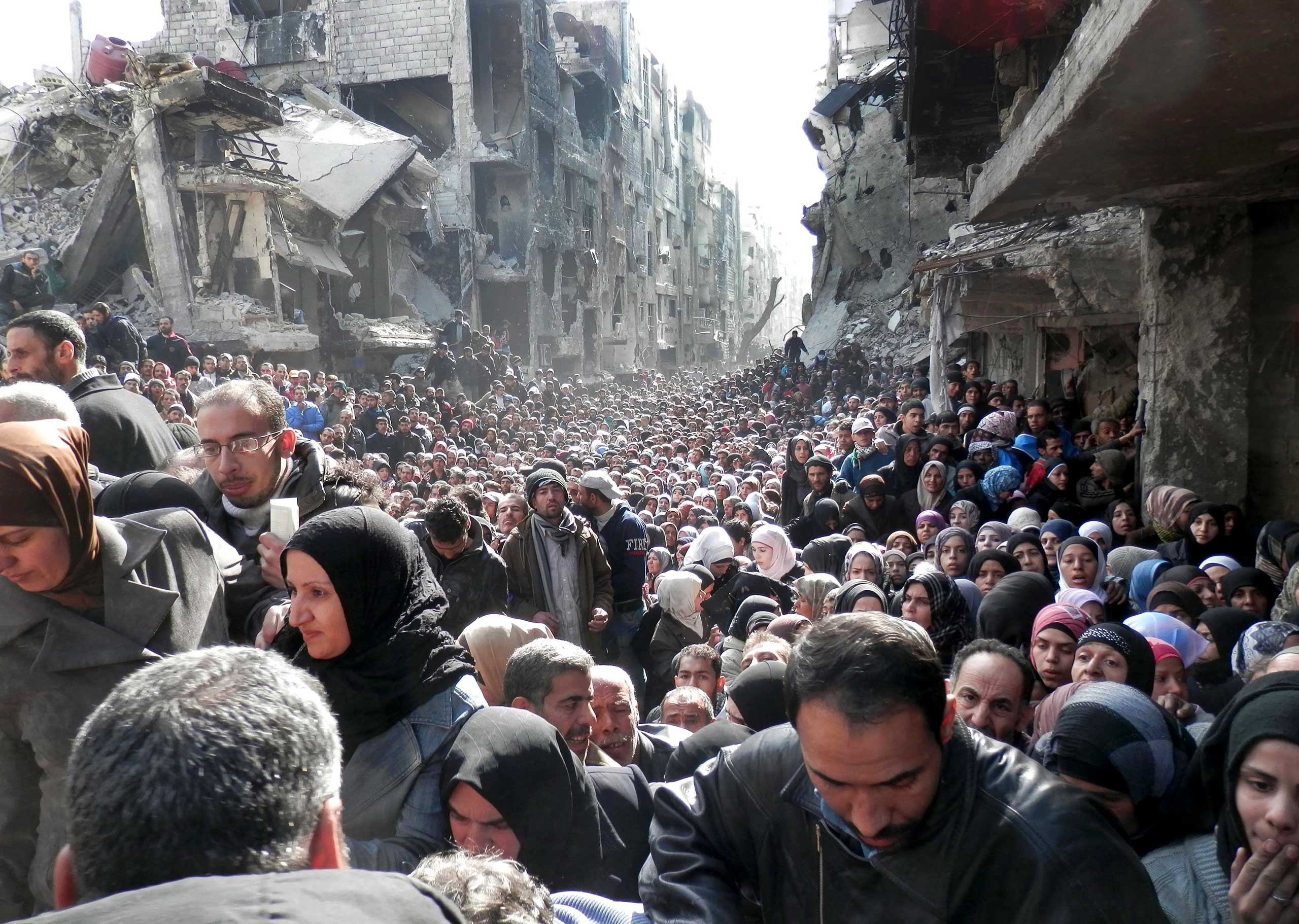 A handout photo of Palestinian refugees waiting for food aid in the Yarmouk camp on the outskirts of Damascus, Syria, Jan. 31, 2014.