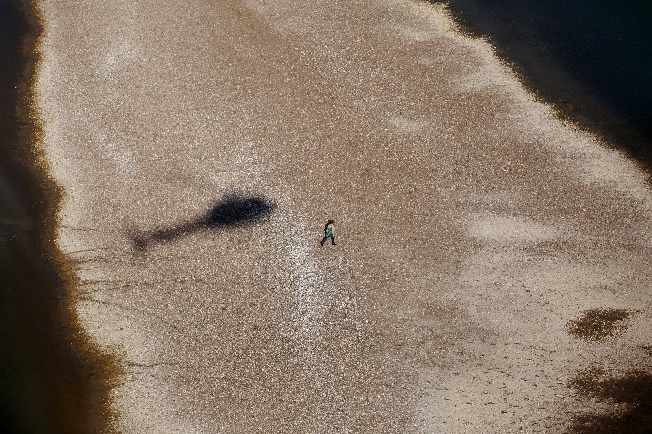 A suspected migrant runs back to Miguel Aleman, Mexico after being pursued by agents near Roma, Texas, Oct. 8, 2014.