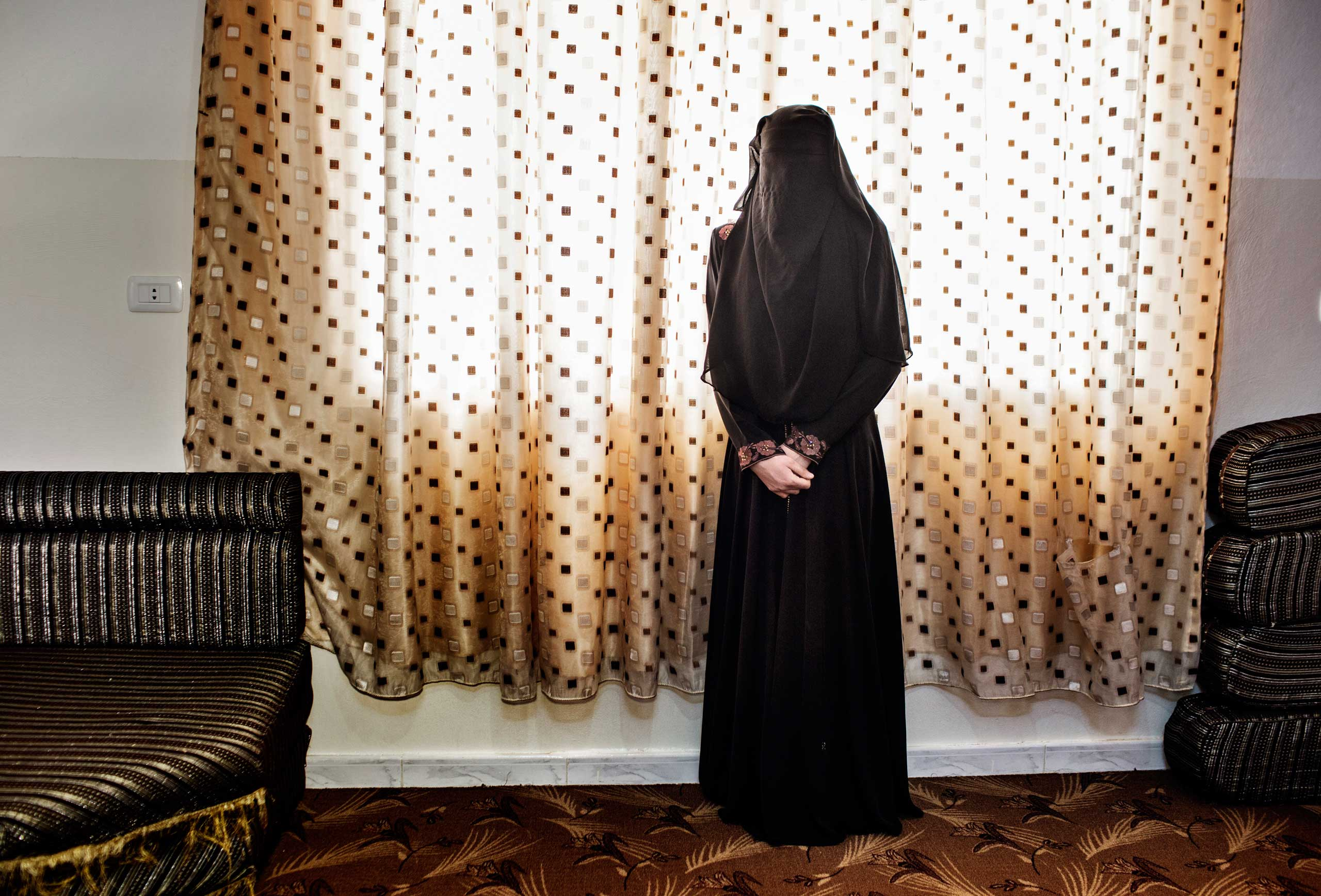 A Syrian refugee woman stands alone in the niqab she recently started wearing. Her 17 year old sister has just married, leaving her alone in the house with her widowed mother and four siblings. The marriage proposals are already coming to her. She had dreamt of finishing high school and becoming a teacher. Ramtha, Jordan, June 1, 2014.