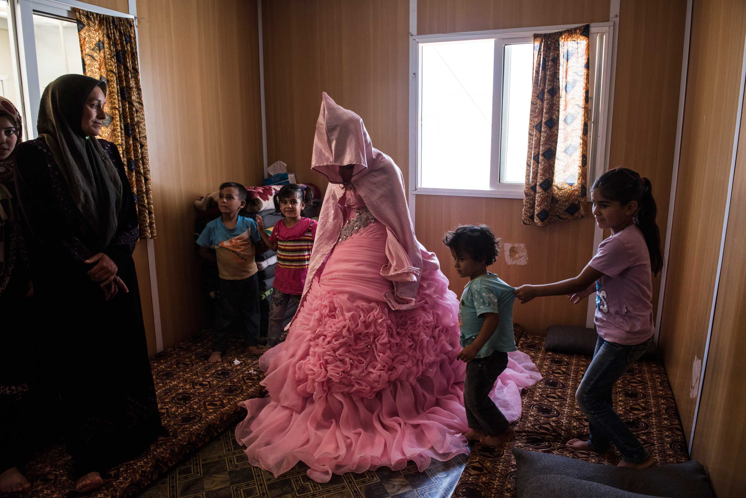 Rahaf Yousef, 13, a Syrian refugee from Daraa, poses for a portrait in her family's trailer as she is surrounded by female relatives on the day of her engagement party at the Zaatari refugee camp in Jordan, Aug. 29, 2014.